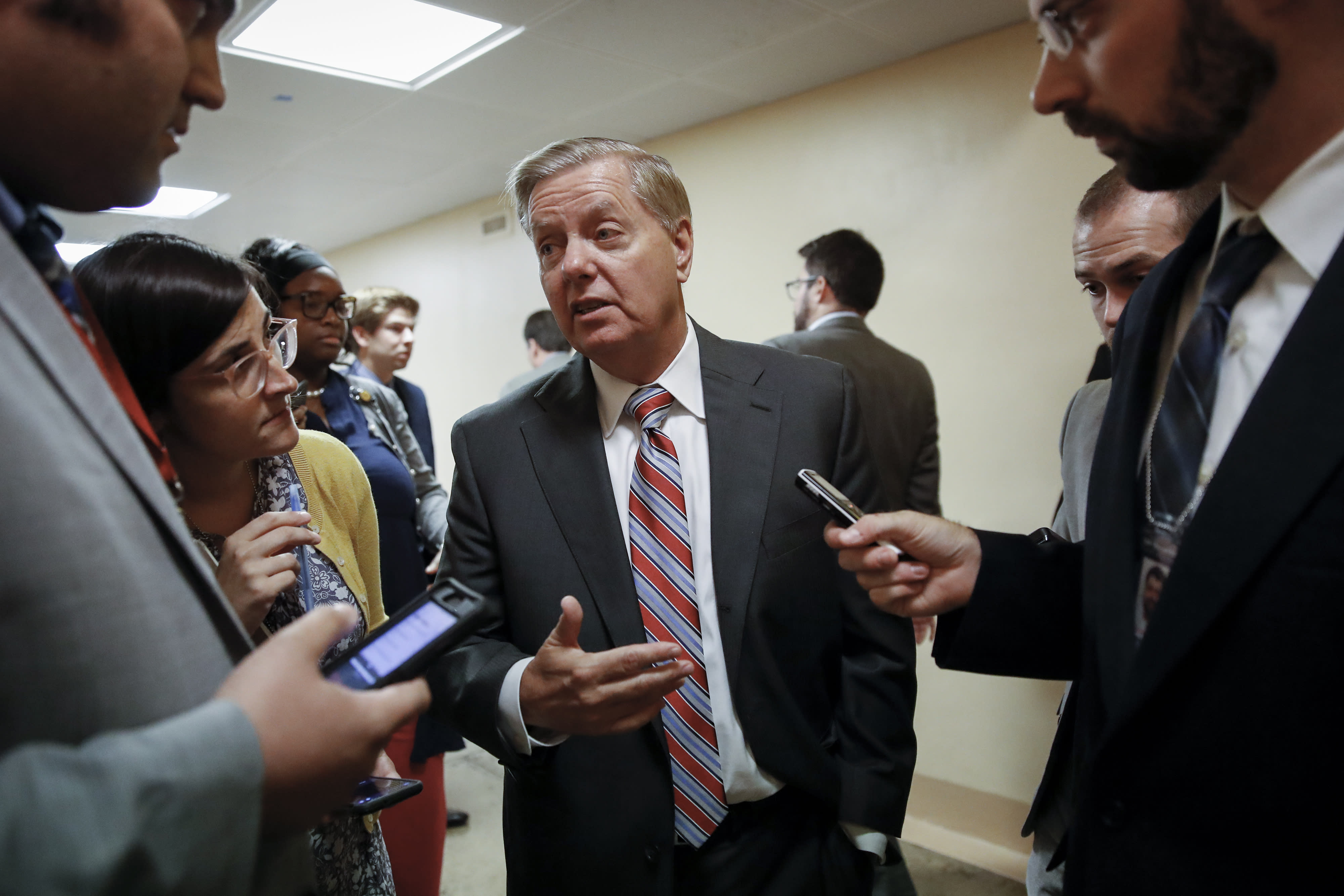 Senate Judiciary Committee Chairman Lindsey Graham, R-S.C., talks to reporters on his way to the Senate chamber for votes on federal judges as a massive budget pact between House Speaker Nancy Pelosi and President Donald Trump is facing a key vote in the GOP-held Senate later, at the Capitol in Washington, Wednesday, July 31, 2019. (AP Photo/J. Scott Applewhite)