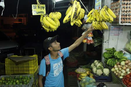 Marlon Carrillo buys fruits to resell them in Colombia, at a market in Rubio, Venezuela December 15, 2017. REUTERS/Carlos Eduardo Ramirez