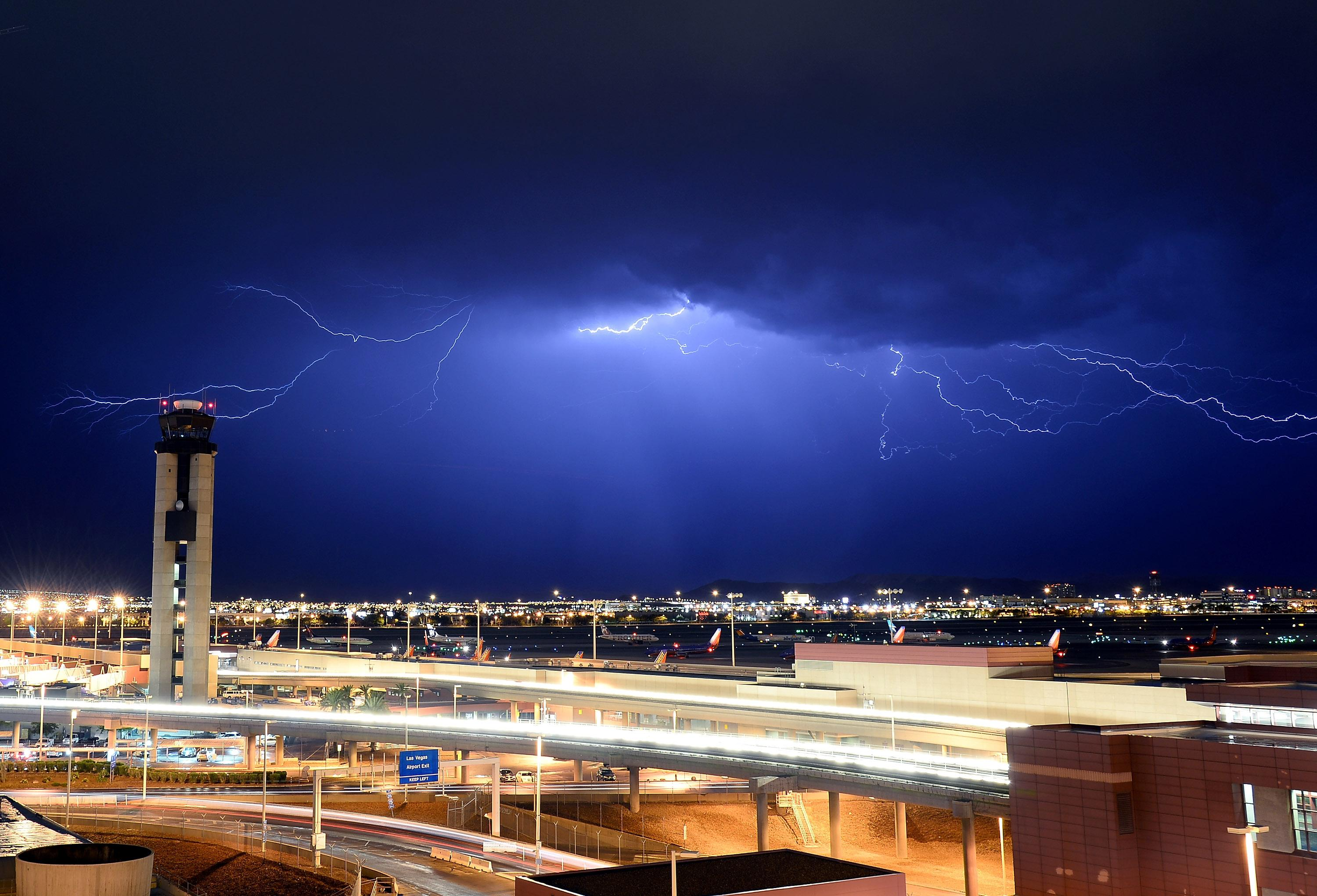 Lightning flashes behind an air traffic control tower at McCarran International Airport on August 18, 2013 in Las Vegas, Nevada (AFP Photo/Ethan Miller)