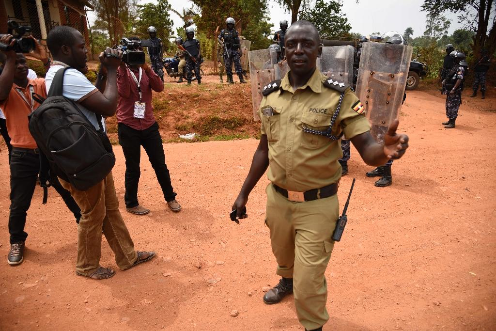 Police officers push back journalists on the drive way to the home of opposition leader, Kizza Besigye, in the Kampala suburb of Kasangati on February 20, 2016 (AFP Photo/Isaac Kasamani)