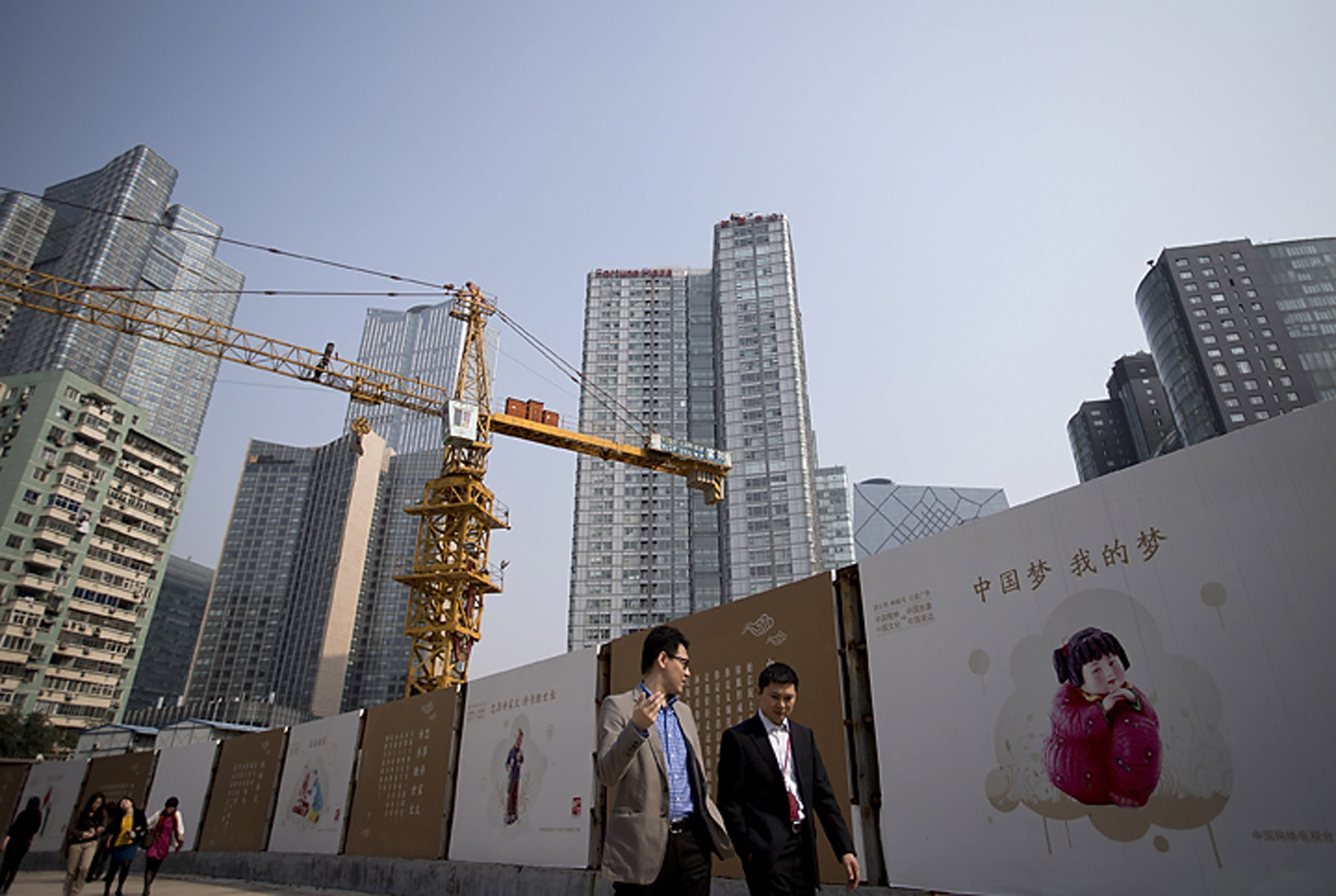FILE - In this Oct. 8, 2013 file photo, office workers walk past China Dream propaganda boards, showing messages pushed by the current Chinese President Xi Jinping's administration, on display near a construction site in Beijing, China. Economists fear a lending bubble in China could threaten the global economy unless the Chinese government shores up its financial system, according to an Associated Press survey. (AP Photo/Andy Wong, File)