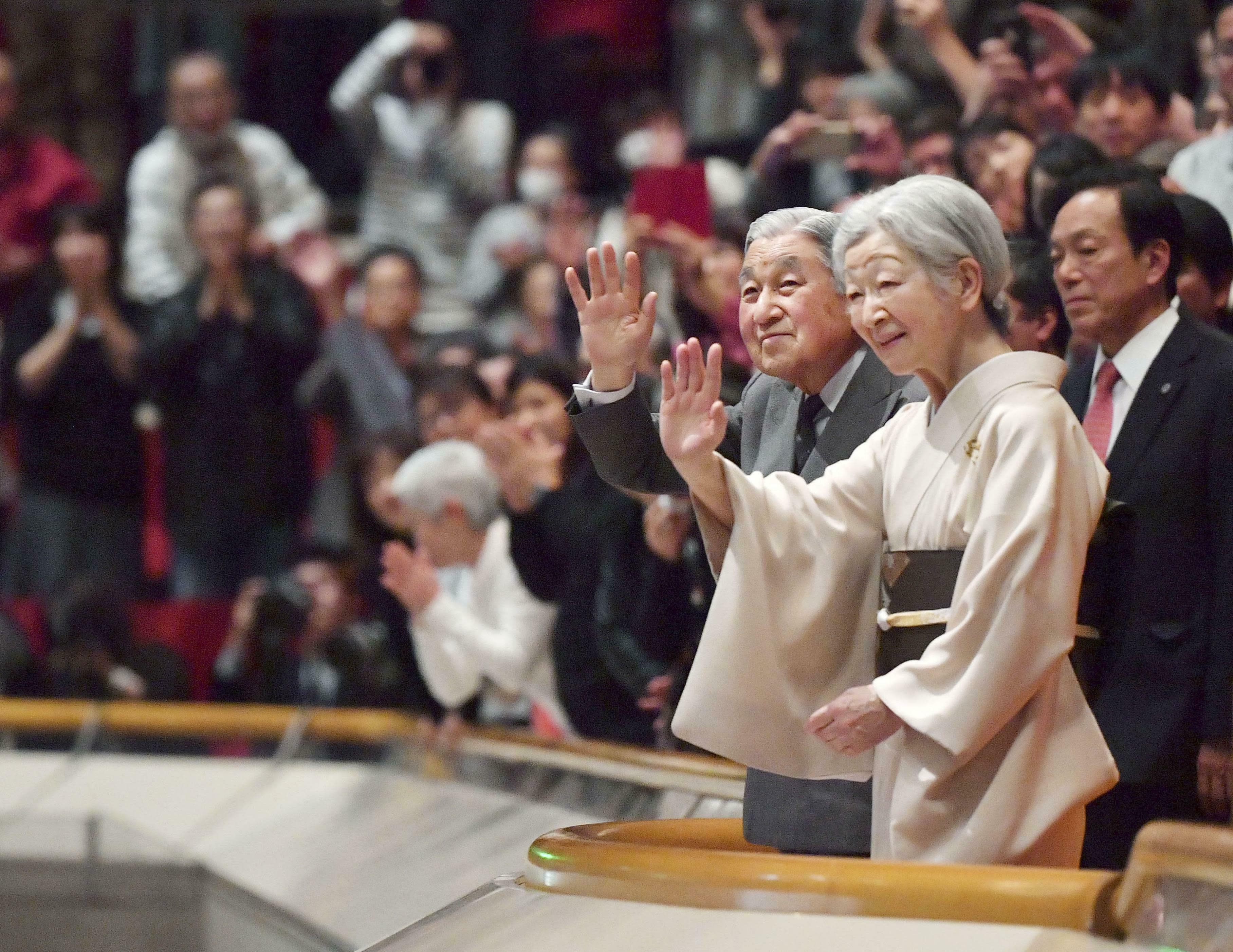 In this Jan. 20, 2019, photo, Japanese Emperor Akihito, front left, and Empress Michiko, front right, acknowledge the crowd during their visit to the New Year Grand Sumo Tournament at Ryogoku Kokugikan in Tokyo. The love many in Japan feel for Akihito was on full display when he made his last official visit to the winter sumo tournament earlier this year. A huge crowd of people leapt to their feet, whooping and grinning as they held up babies and waved flags.(Kyodo News via AP)