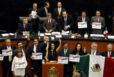 "Senators of the Party of the Democratic Revolution (PRD) hold placards reading ""No to the privatization of Pemex"" while interrupting a debate on an energy reform bill at the Senate in Mexico City December 9, 2013. REUTERS/Henry Romero"