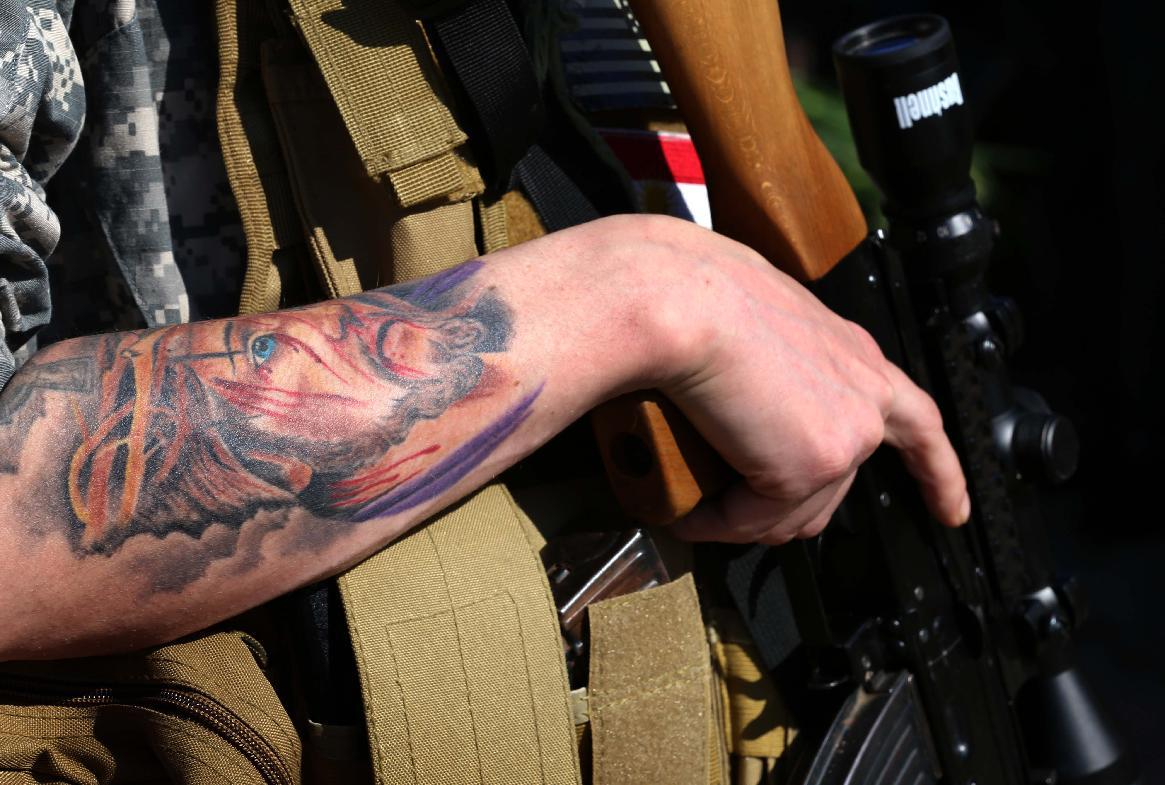 """Christian militia volunteer """"Brett"""" has a tattoo of a machinegun on his left arm and another of Jesus in a crown of thorns on his right (AFP Photo/Safin Hamed)"""