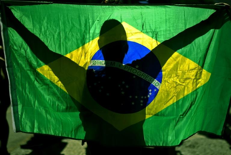A supporter of Brazil President Jair Bolsonaro displays the country's flag at a demonstration in Rio de Janeiro in June 2020 during the coronavirus pandemic (AFP Photo/CARL DE SOUZA)