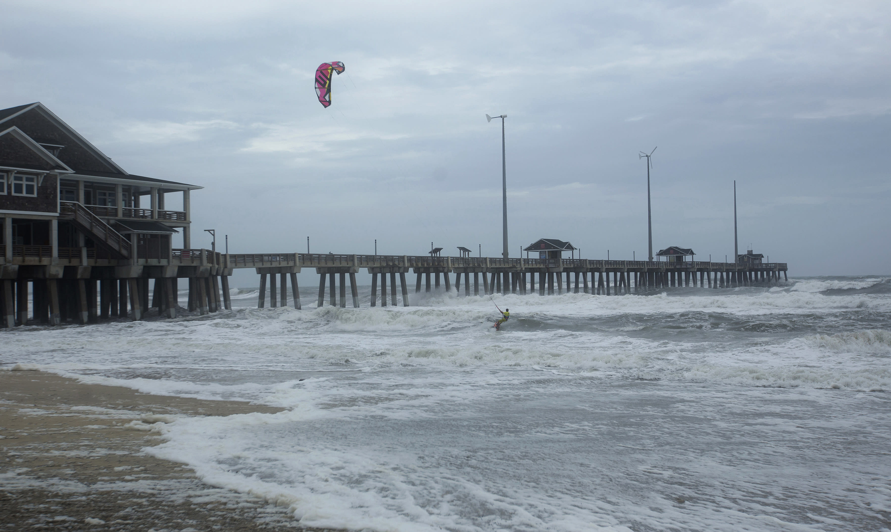 Kite Boarder Dimitri Maramenides heads out next to Jennette's Pier in Nags Head, N.C., as Hurricane Florence makes landfall further south on Friday, Sept, 14, 2018. (L. Todd Spencer/The Virginian-Pilot via AP)