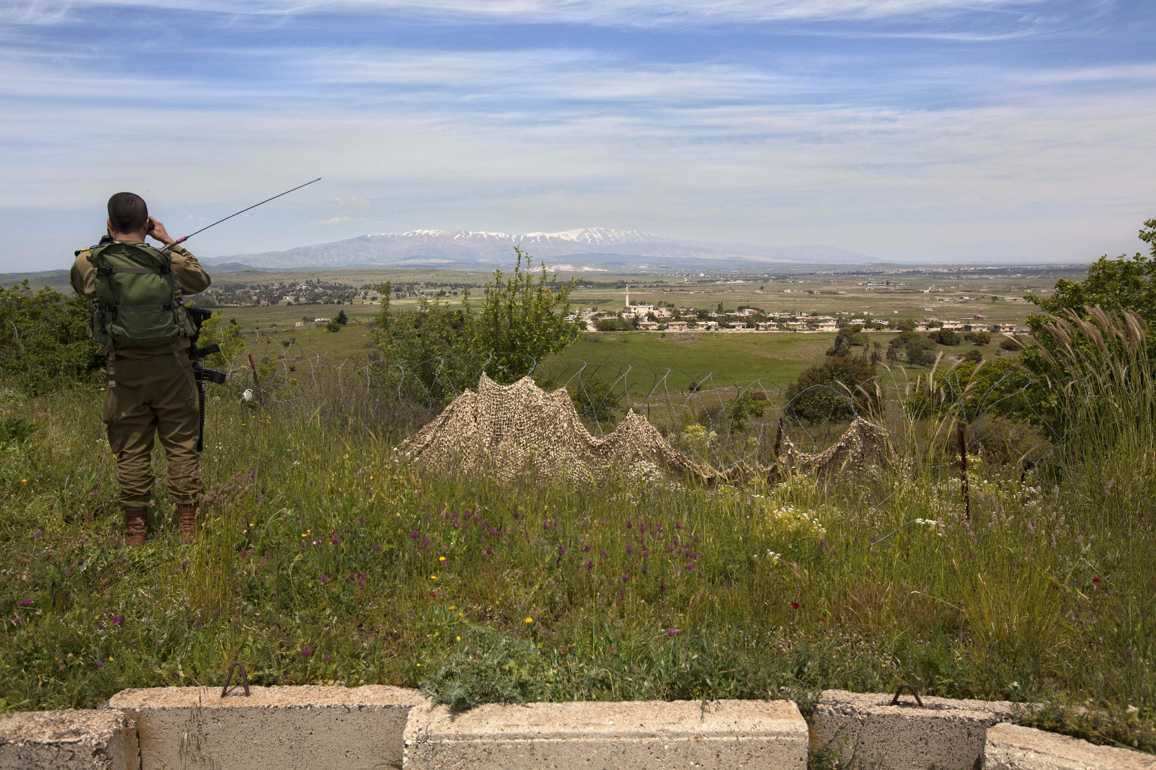 In this photo taken Wednesday, April 24, 2013, an Israeli soldier looks through binoculars at a Syrian village from an army post on the border between Israel and Syrian on the Golan Heights. Against a breathtaking vista of green fields and a snowcapped mountain range, all is silent but for a strong gust of wind whipping across the landscape. The tranquility is suddenly interrupted by a burst of gunfire from beyond a newly built fortified fence: Jihadi rebels are battling with Bashar Assad's battered troops in a nearby Syrian village. Watching it all unfold are Israeli soldiers atop tanks - a sight unseen here in a generation - and the sounds of explosions from a large-scale Israeli drill are distinctly heard in the background. (AP Photo/Sebastian Scheiner)
