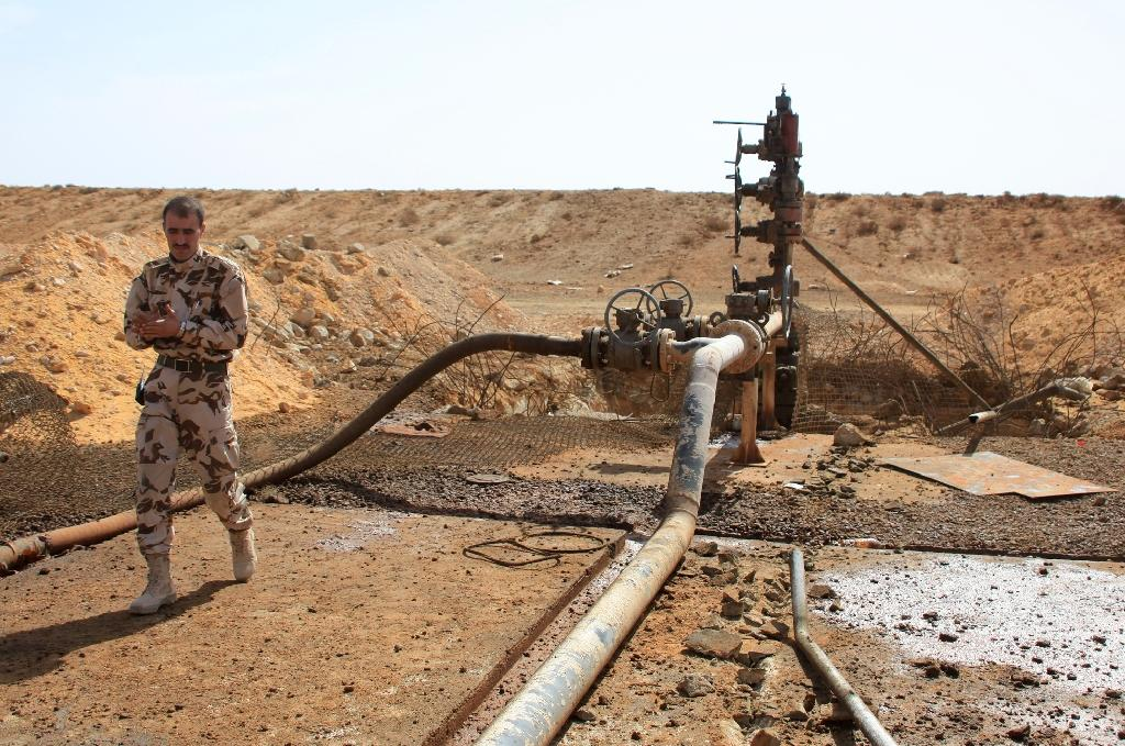 A member of the Syrian government forces walks next to a well at Jazel oil field, near the ancient city of Palmyra in the east of Homs province in March