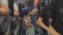 Fist-bumping 2-year-old boards airplane in style