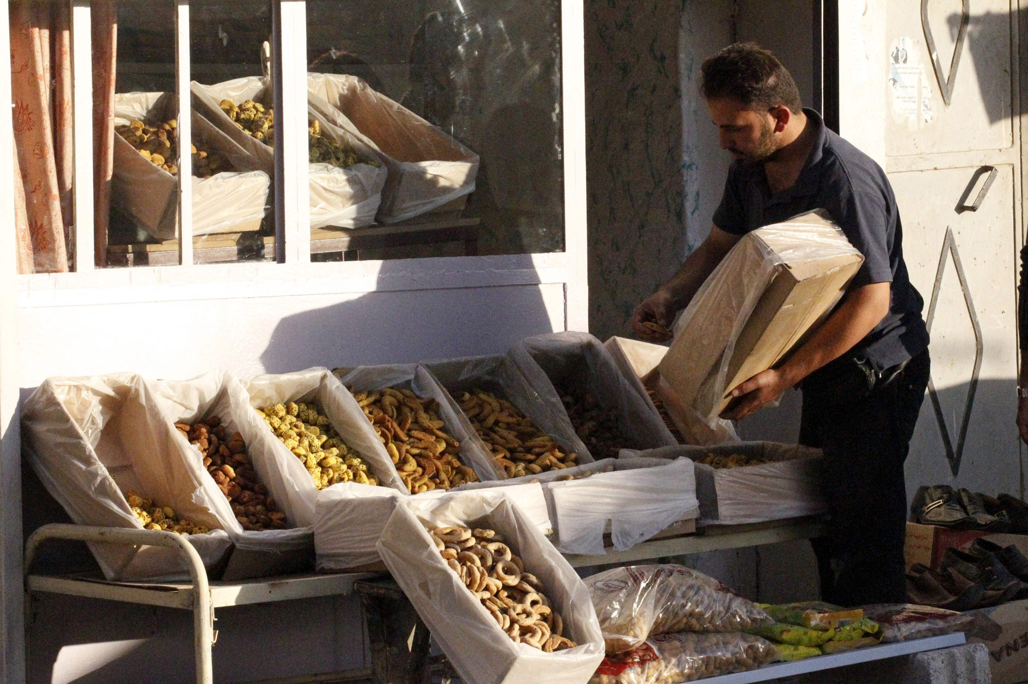A man arranges sweets into boxes in a market ahead of the upcoming Muslim Eid al-Adha holiday in Manbej, in Aleppo countryside October 12, 2013. Picture taken October 12, 2013. REUTERS/Nour Fourat (SYRIA - Tags: RELIGION FOOD)