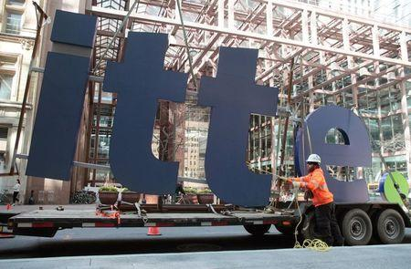 A worker guides part of a Deloitte sign before its installation on a new office building in downtown Toronto