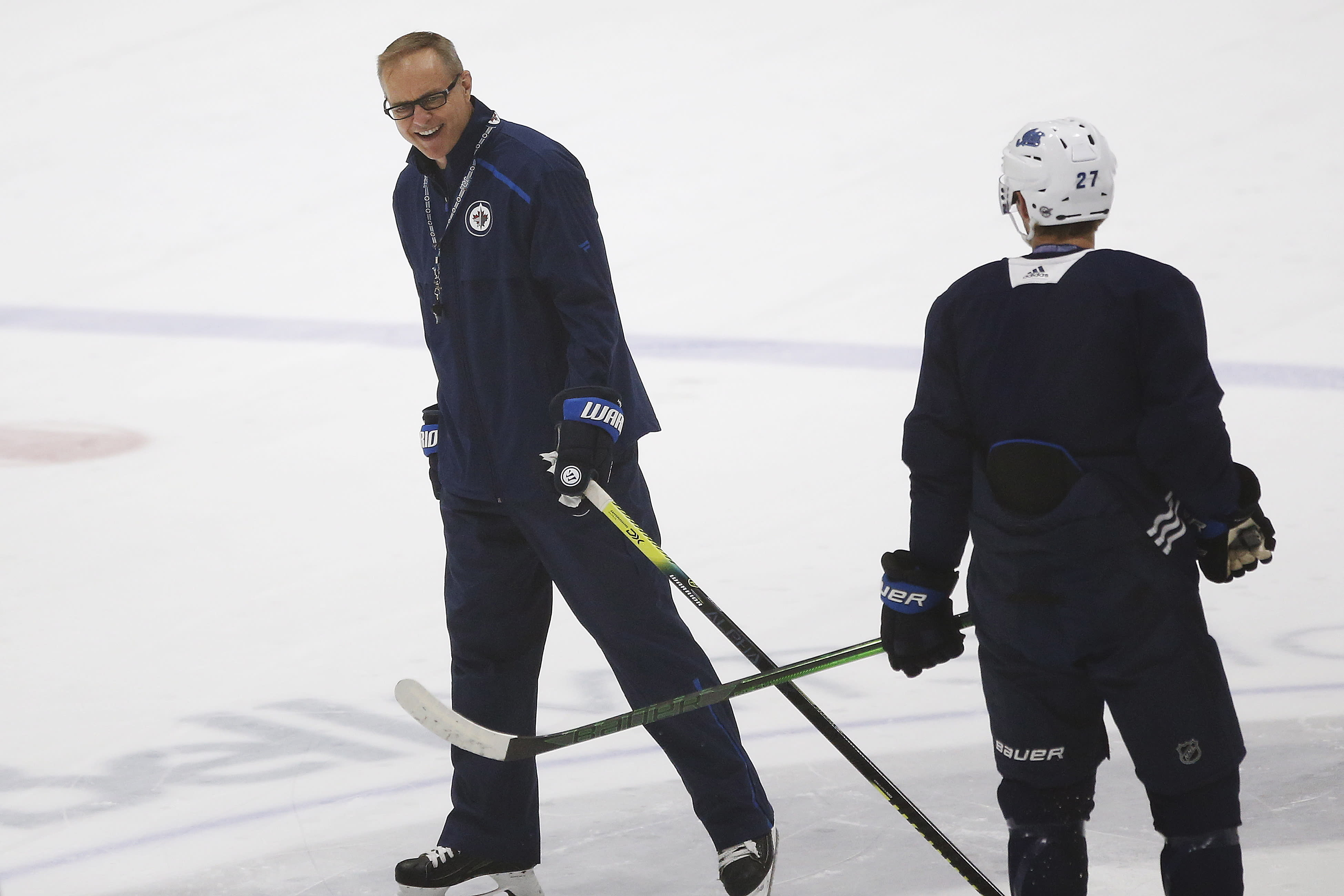 Winnipeg Jets' head coach Paul Maurice and Nikolaj Ehlers (27) joke during the first day of the Jets NHL summer training camp as the NHL reopens during COVID-19 in Winnipeg, Monday, July 13, 2020. (John Woods/The Canadian Press via AP)