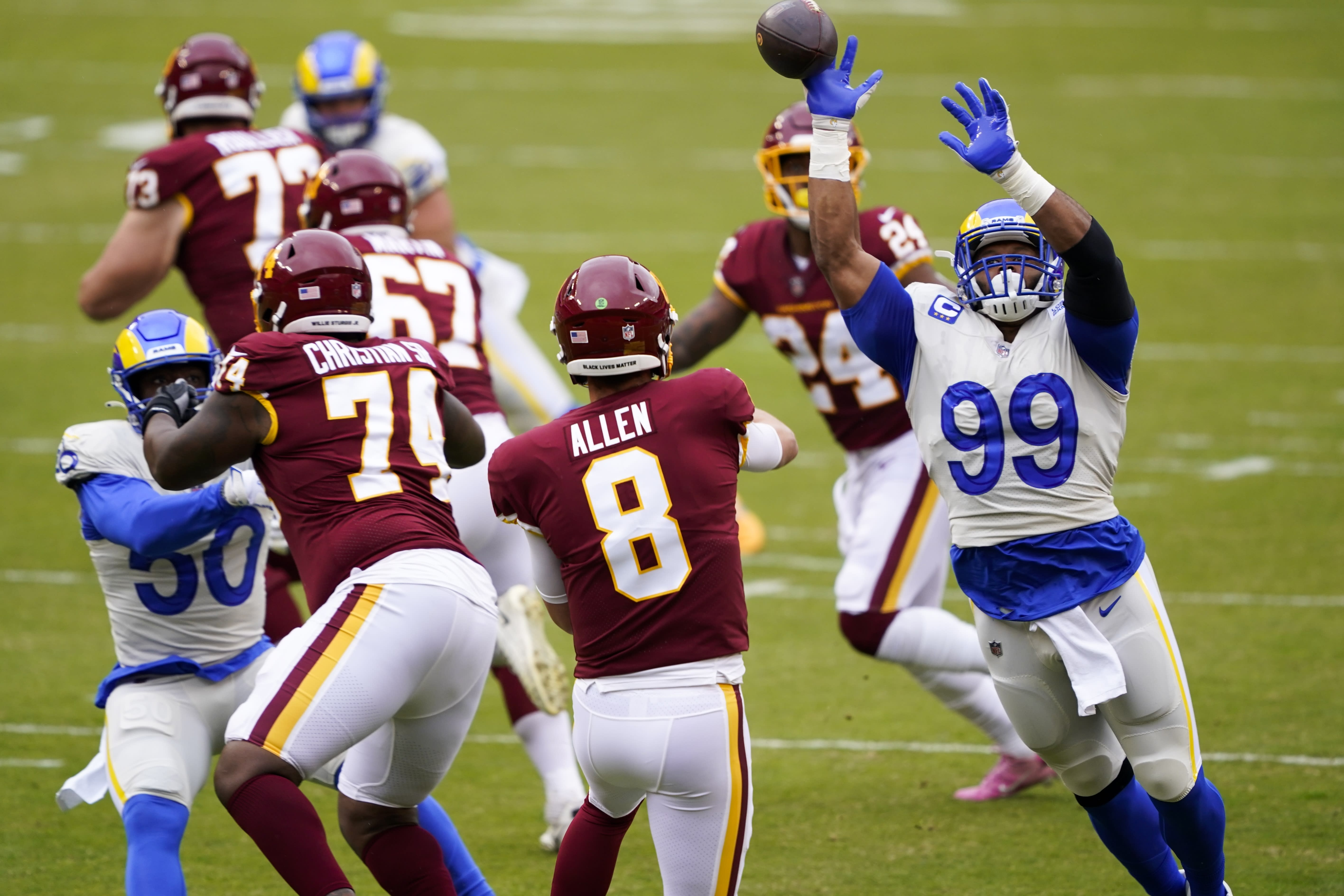 Washington Football Team's Kyle Allen throws with Los Angeles Rams' Aaron Donald rushing during the first half of an NFL football game Sunday, Oct. 11, 2020, in Landover, Md. (AP Photo/Susan Walsh)