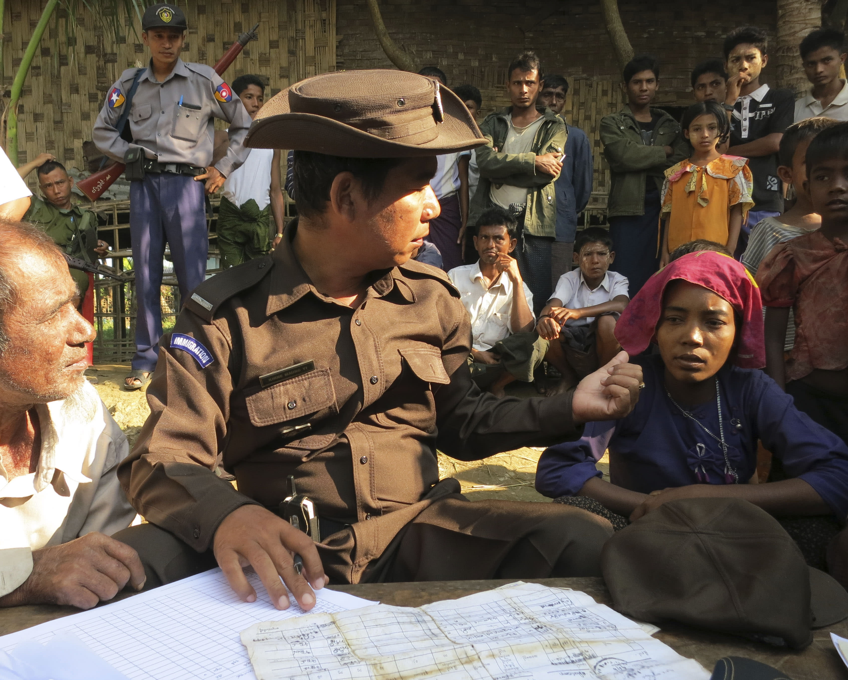 In this Nov. 10, 2012 photo, an immigration officer fills out forms during an operation to verify the citizenship of Muslims living in the western Myanmar village of Sin Thet Maw. The government launched the checks on Nov. 8 after unrest broke out in June between ethnic Rakhine Buddhists and Rohingya Muslims they view as foreigners from Bangladesh. (AP Photo/Todd Pitman)