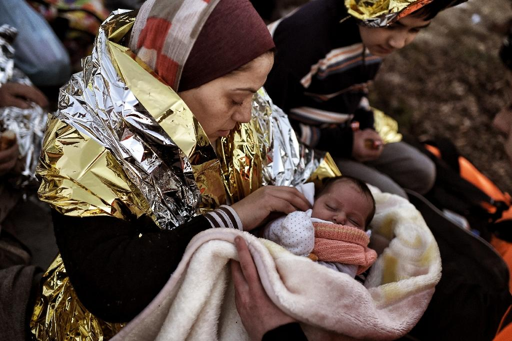 A migrant holds her baby after arriving on the Greek island of Lesbos, after crossing the Aegean Sea from Turkey, on February 28, 2016 (AFP Photo/Aris Messinis)