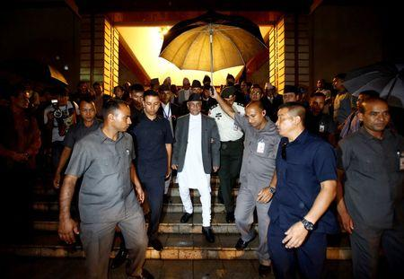 Nepal's Prime Minister Khadga Prasad Sharma Oli, also known as KP Oli, walks out from the parliament after announcing his resignation in Kathmandu