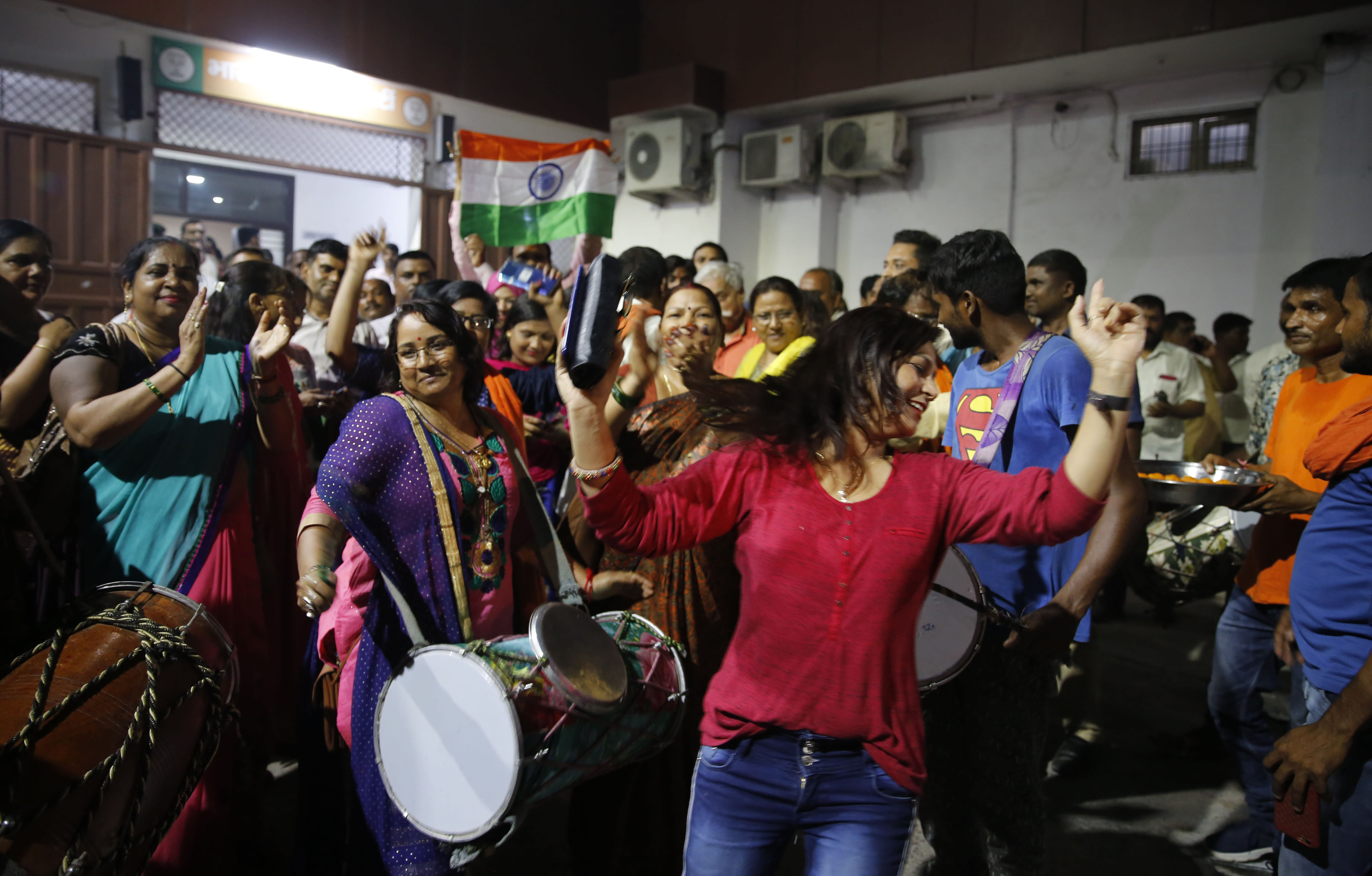 Supporters of India's ruling Bharatiya Janata Party (BJP) celebrate the government revoking Kashmir's special status, in Lucknow, India, Tuesday, Aug. 6, 2019. Indian lawmakers passed a bill Tuesday that strips the statehood from the Indian-administered portion of Muslim-majority Kashmir amid an indefinite security lockdown in the disputed Himalayan territory, actions that neighboring Pakistan warned could lead to war. (AP Photo/Rajesh Kumar Singh)