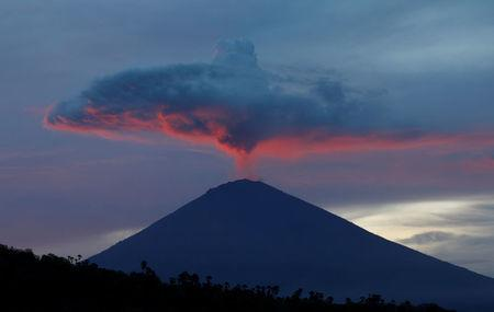 A plume of smoke above Mount Agung volcano is illuminated at sunset as seen from Amed, Karangasem Regency, Bali