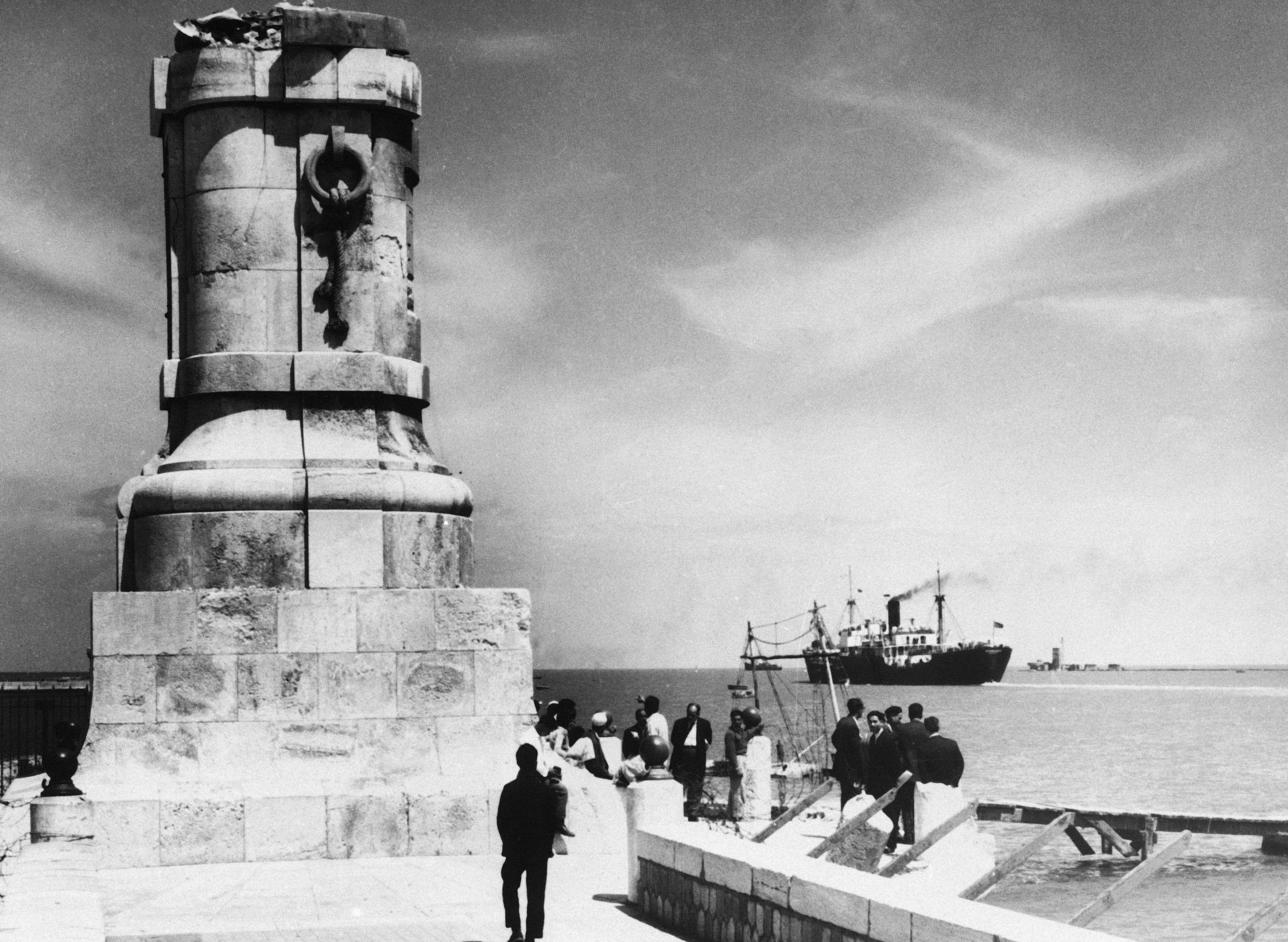 """FILE - This March 30, 1957 file photo, shows the base of the statue of Suez Canal builder Ferdinand de Lesseps is all that remains at Port Said, Egypt, after control of the canal was seized by Egyptian President Nasser in 1956. A proposal to bring back the statue has stirred controversy in Egypt with many saying it would be a salute to colonial times and a """"humiliation"""" to the memory of tens of thousands of Egyptian laborers who died while digging the waterway. The debate started when a newspaper reported in June 2020 that local authorities in the Mediterranean province of Port Said were thinking of returning the statue to where it once stood at the northern entrance of the canal. (AP Photo, File)"""