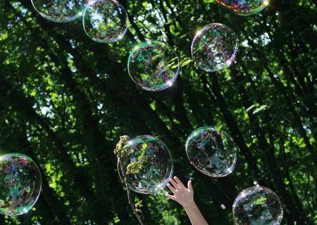 A child plays with soap bubbles at an event to support autistic children and their families in a park in Kiev