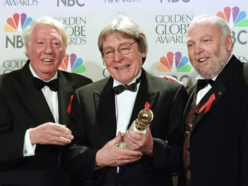 FILE PHOTO: Producer Robert Stigwood (L), director Alan Parker and producer Andrew Vajna (R) celebrate the award
