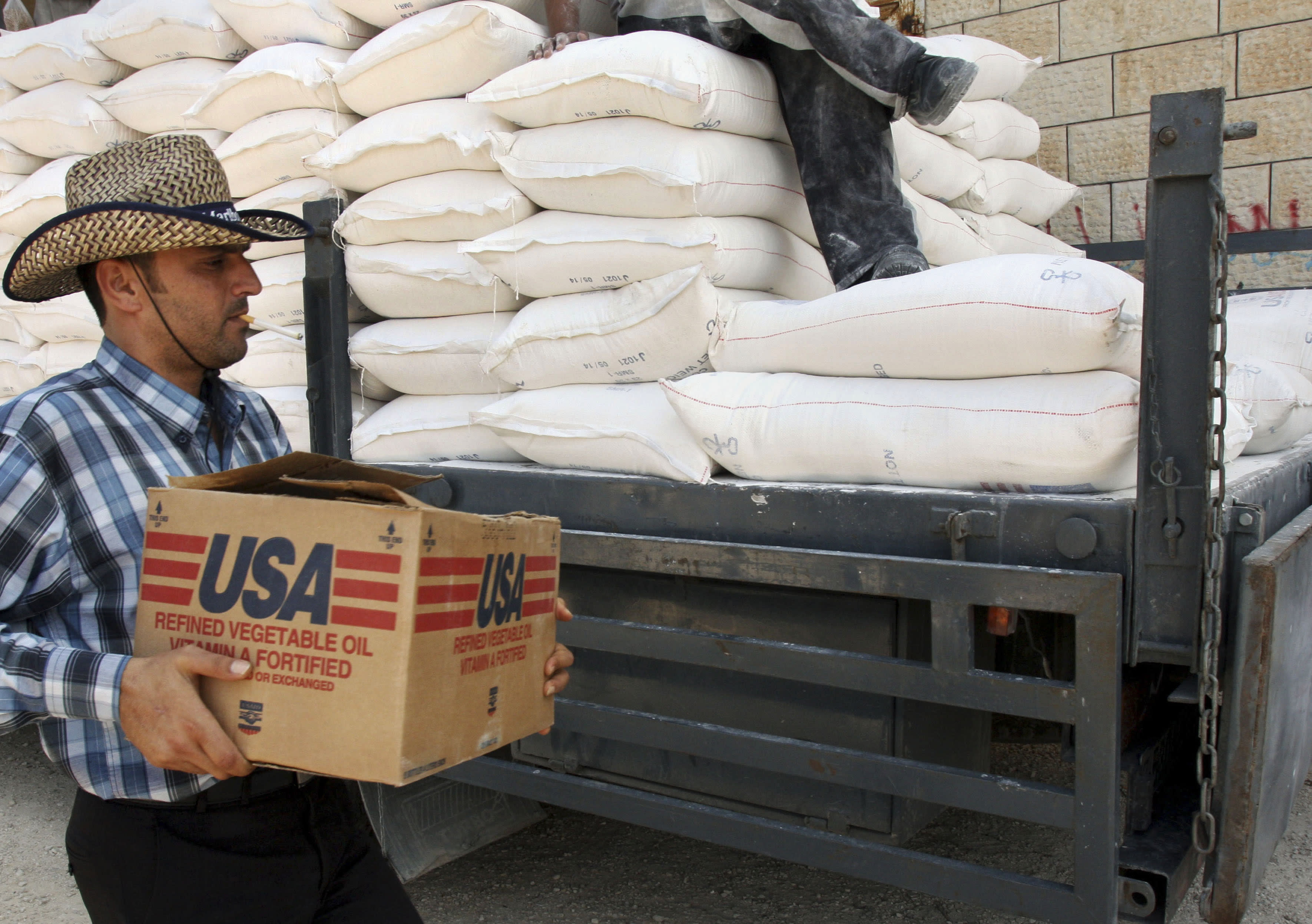 FILE - In this June 4, 2008 file photo, a Palestinian carries a box of vegetable oil as he walks past bags of flour, both donated by the United States Agency for International Development, at a depot in the West Bank village of Anin near Jenin. Tens of thousands of Palestinians are no longer getting food aid or health services from America after the Trump administration's decision in 2018 to cut more than $200 million in aid to the Palestinians. Before the aid cuts were announced, it provided food aid -- branded as a gift from the American people -- to more than 180,000 Palestinians in the Israeli-occupied West Bank and Gaza on behalf of the World Food Program. (AP Photo/Mohammed Ballas, File)