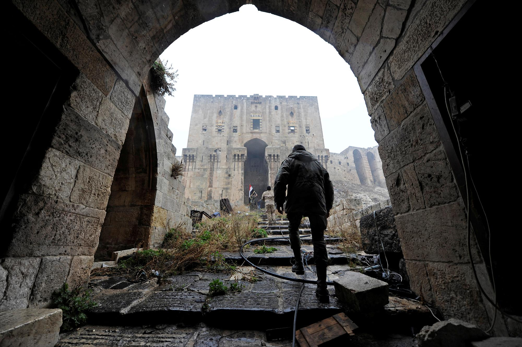 <p>Forces loyal to Syria's President Bashar al-Assad walk inside Aleppo's historic citadel, during a media tour, Syria on Dec.13, 2016. (Omar Sanadiki/Reuters) </p>