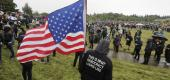"""A protester holds a United States flag while wearing a jacket that reads """"This is What Democracy Looks Like."""" (AP)"""