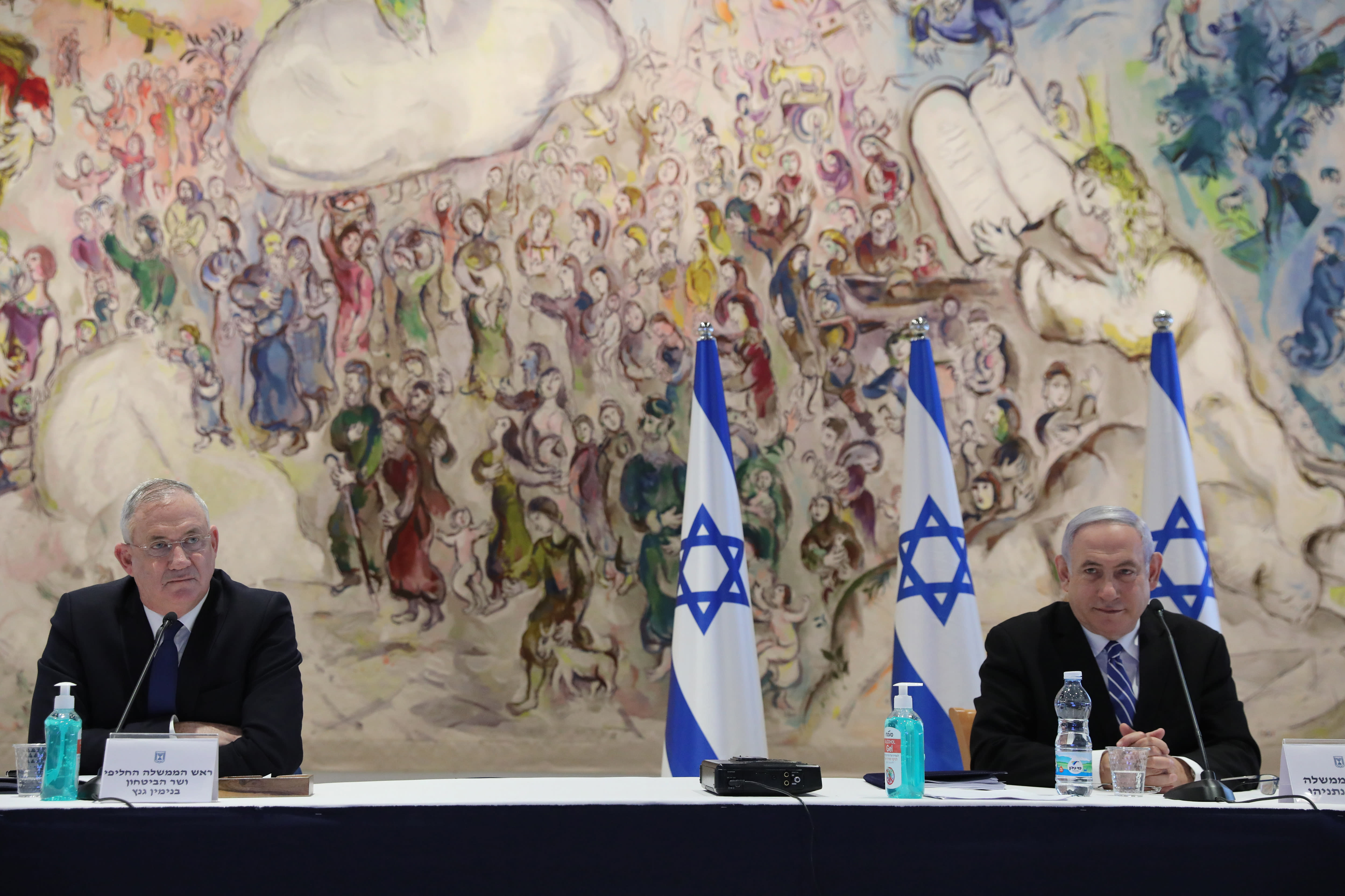 Israeli Prime Minister Benjamin Netanyahu, right, and Defense Minister Benny Gantz attend the first Cabinet meeting of the new government at the Chagall Hall in the Knesset, the Israeli Parliament in Jerusalem, Israel, Sunday, May 24, 2020. (Abir Sultan/Pool Photo via AP)