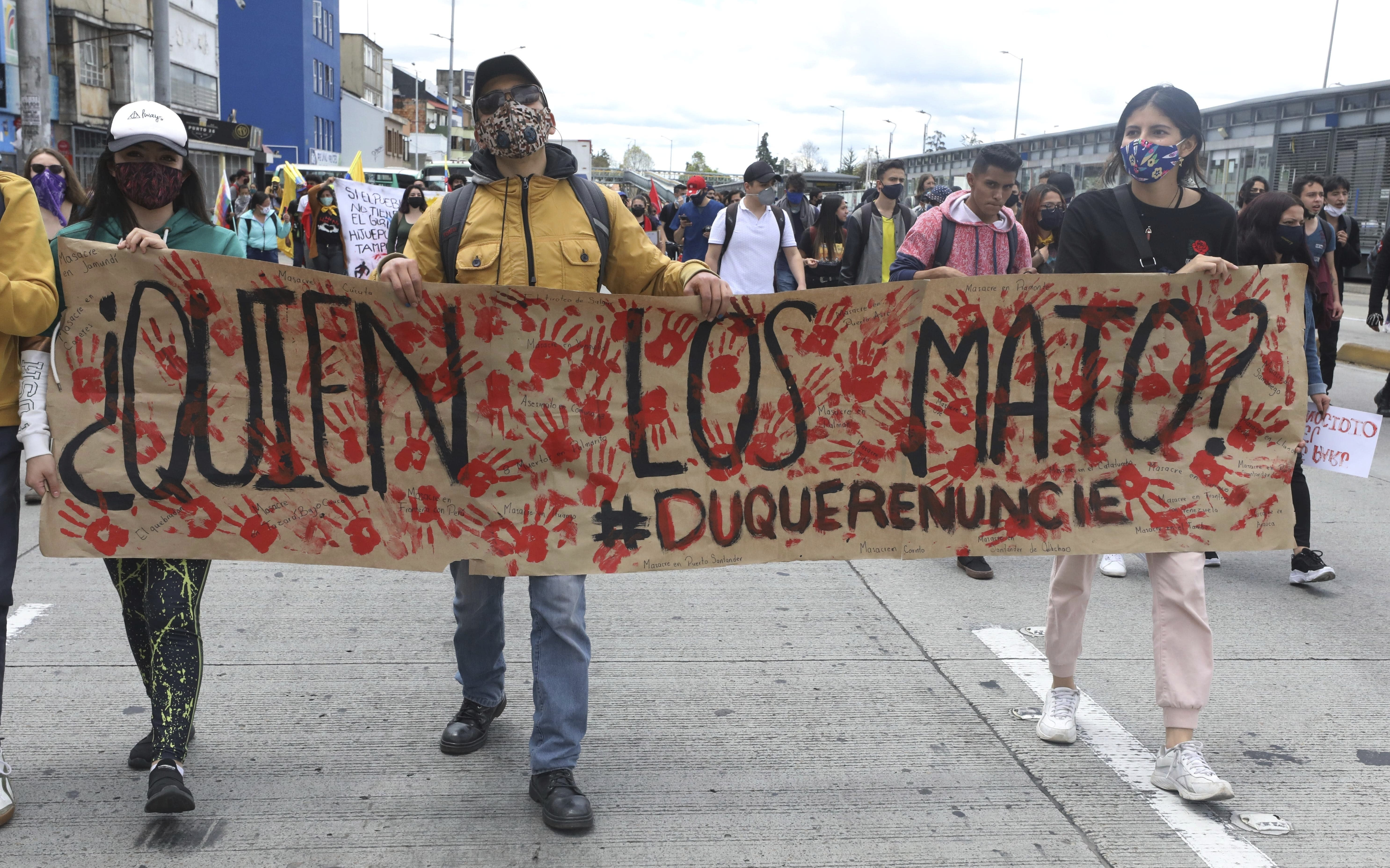 """University students march holding a poster with a message that reads in Spanish: """"Who killed them?"""" during a demonstration against a wave of massacres, in Bogota, Colombia, Monday, Sept. 21, 2020. Rather than a national dispute between guerrillas and the state, violence in rural Colombia is now marked by a patchwork of local feuds between criminal groups who fight over drug routes, illegal mines and even gasoline smuggling routes. (AP Photo/Fernando Vergara)"""