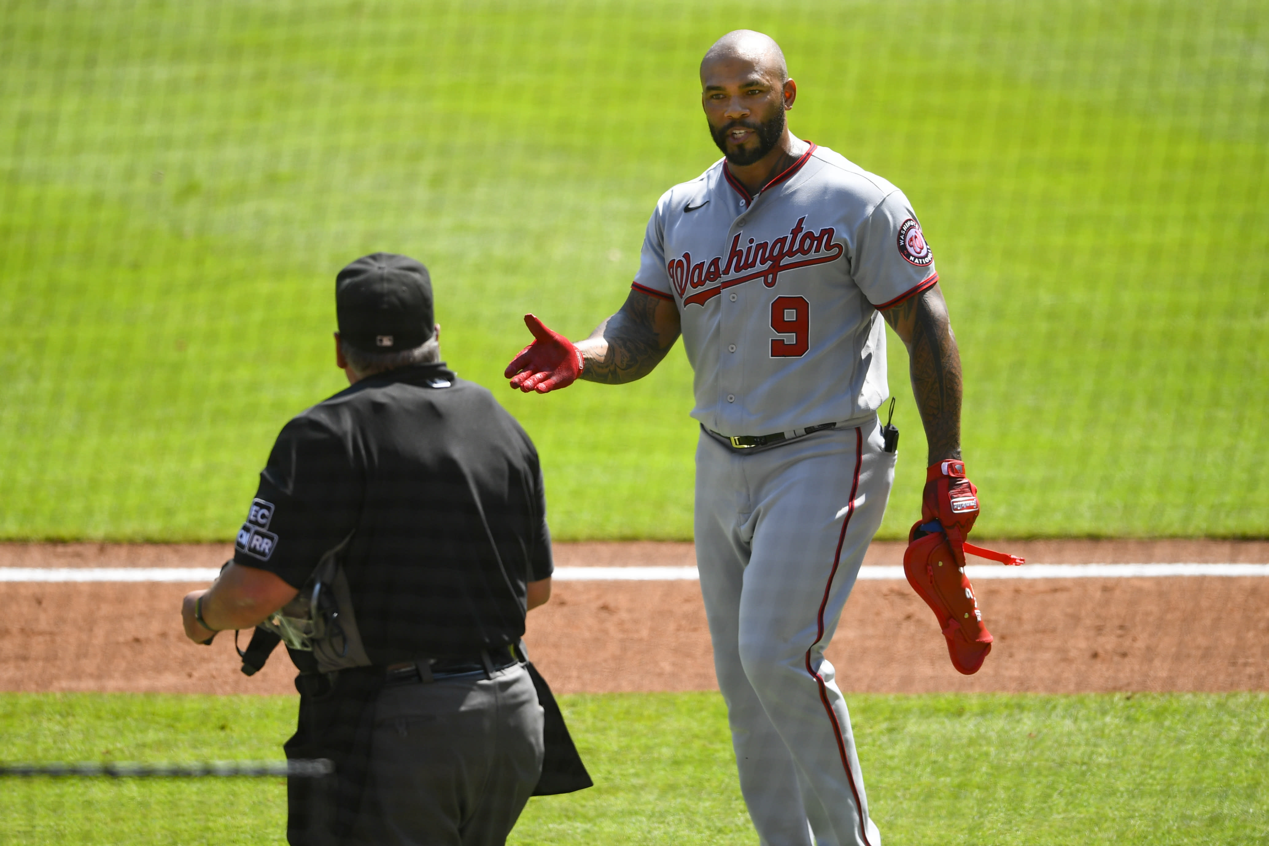 Washington Nationals' Eric Thames talks to an umpire after striking out against the Atlanta Braves during the seventh inning of a baseball game Sunday, Sept. 6, 2020, in Atlanta. (AP Photo/John Amis)