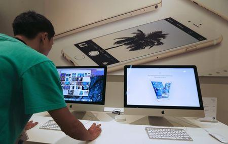 A sales assistant shows features of iOS 9 on an Apple iMac at an Apple reseller shop in Bangkok