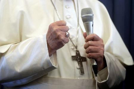FILE PHOTO: Pope Francis speaks with the media onboard a plane during his flight back from a trip in Dublin
