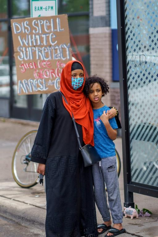 A Somali American mother and her child stand during a protest in Minneapolis against the death of George Floyd -- Minnesota has the highest percentage of refugees per inhabitant in the US, and many are from the Horn of Africa (AFP Photo/kerem yucel)