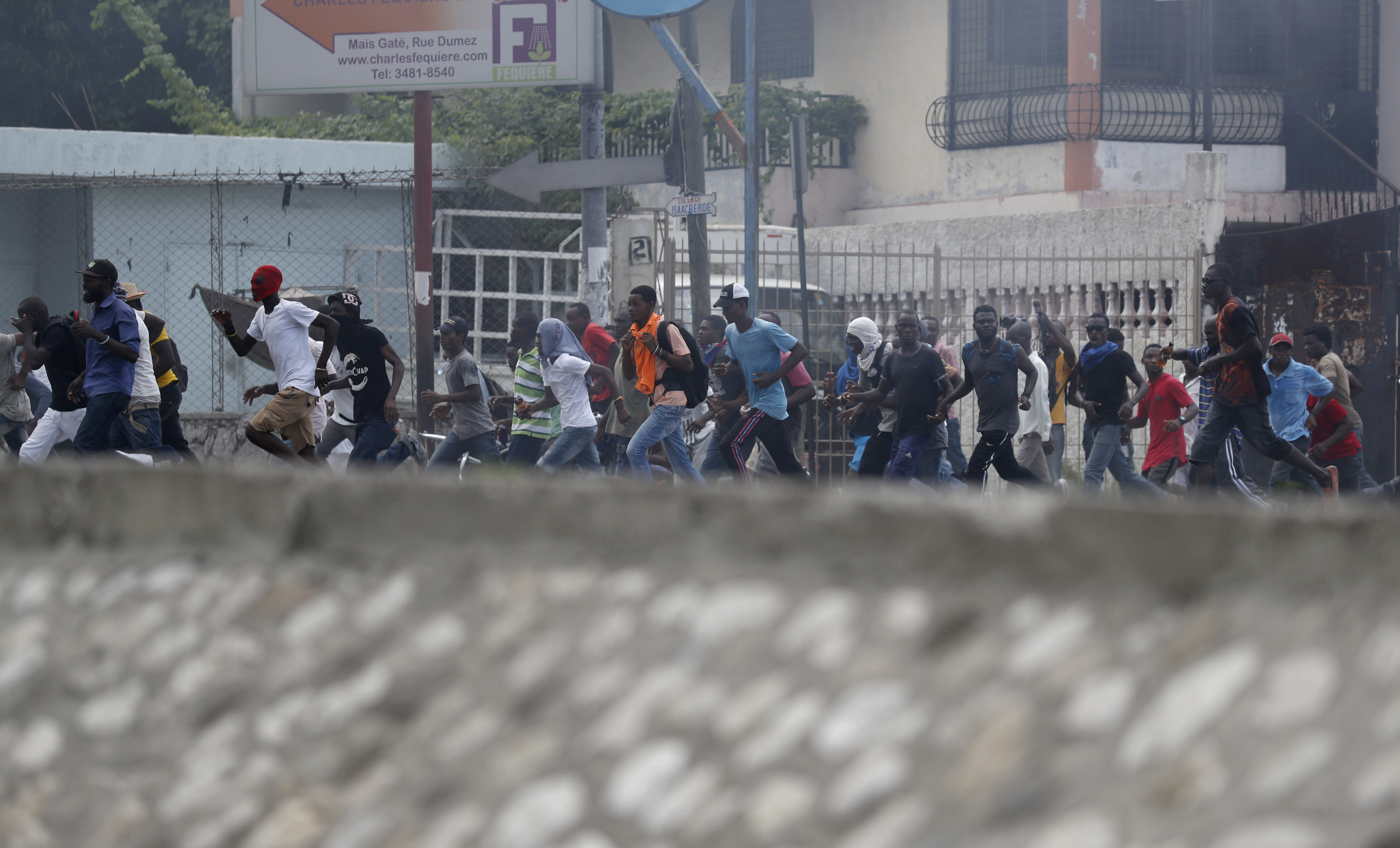Protestors calling for the resignation of President Jovenel Moise run during clashes with the police in Port-au-Prince, Haiti, Friday, Oct. 4, 2019. After a two-day respite from the recent protests that have wracked Haiti's capital, opposition leaders urged citizens angry over corruption, gas shortages, and inflation to join them for a massive protest march to the local headquarters of the United Nations.(AP Photo/Rebecca Blackwell)