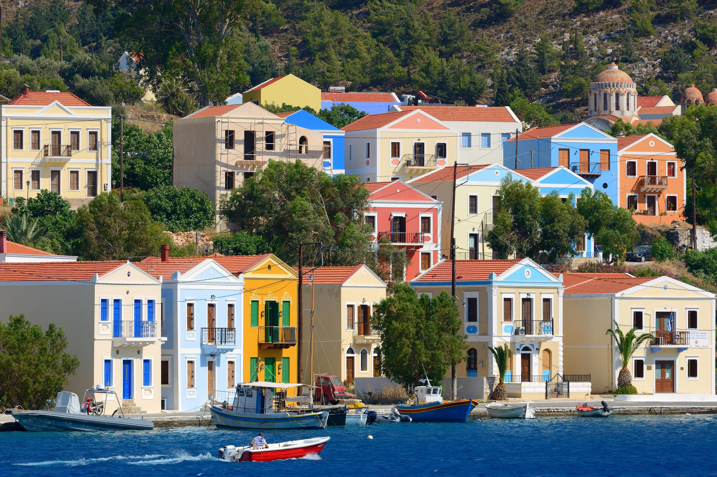 """<p>The pretty island of Kastellorizo, which lies 110km east of <a href=""""http://travel.aol.co.uk/guides/rhodes/"""" target=""""_blank"""">Rhodes</a>, has a main town that unfolds around the natural harbour with unique architecture and colourful houses. The island's is home to a cluster of islets and offers a wealth of marine life to discover in its clear blue seas. Around the island you'll find cafes, tavernas and shops. The medieval castle and archaeological and folklore museums are several top attractions to visit when you're not at the beach. As tourism is yet to develop you'll only find a selection of hotels - a good place to experience true Greek island life.</p>"""