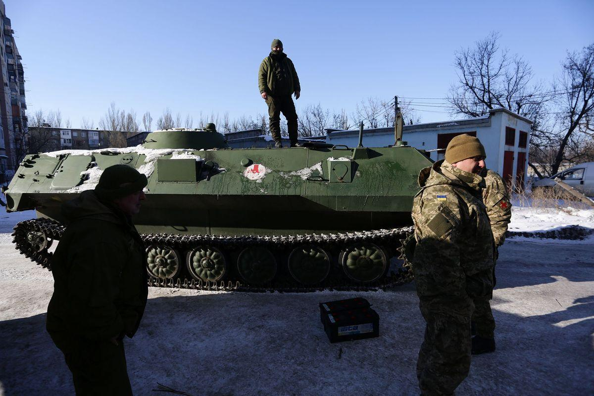 "Ukrainian medical servicemen stand on an Armoured Personnel Carriers (APC) after they carried wounded servicemen to hospital in Ukraine-controlled town of Avdiivka, in Donetsk region on January 30, 2017.A sudden surge in clashes between Ukrainian forces and Russian-backed rebels killed at least six people on January 30, 2017 despite a supposed truce in Ukraine's war-scarred east. The overall death toll for the past two days rose to 11 after the bloodiest outburst of violence since the former Soviet republic and its foes agreed an ""indefinite"" ceasefire last month. The violence coincided with a visit by Ukrainian Petro Poroshenko to Berlin at which he urgend German Chancellor Angela Merket to step up economic sanctions on Russia for its interference in his ex-Soviet State. / AFP / Aleksey FILIPPOV (Photo credit should read ALEKSEY FILIPPOV/AFP/Getty Images)"