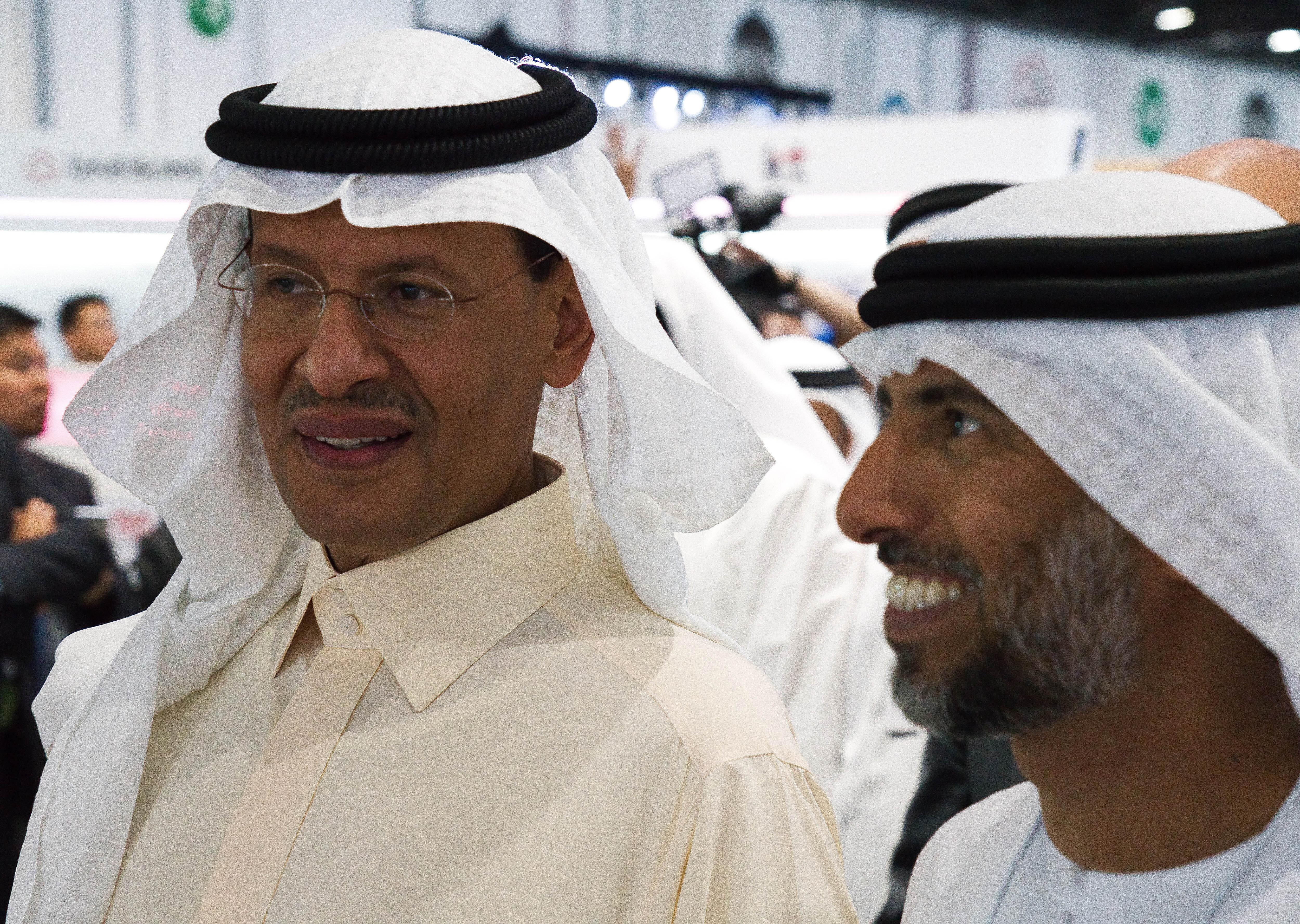 Saudi Arabia's new Energy Minister Prince Abdulaziz bin Salman, left, and United Arab Emirates Energy Minister Suhail al-Mazrouei, right, walk through an energy exhibition in Abu Dhabi, United Arab Emirates, Monday, Sept. 9, 2019. Prince Abdulaziz, as well as the CEOs of Total SA and ENI SpA, were in Abu Dhabi on Monday at the World Energy Congress. (AP Photo/Jon Gambrell)