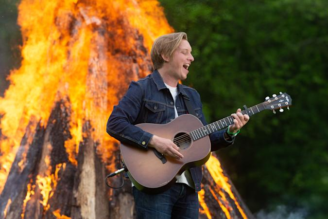 """GLASTONBURY, UNITED KINGDOM - MAY 22: In this image released on May 22nd 2021, George Ezra performs by a fire as part of the Glastonbury Festival Global Livestream """"Live at Worthy Farm"""" at Worthy Farm, Pilton on May 21, 2021 in Glastonbury, England. The five hour special production has been filmed across Glastonbury Festivals Worthy Farm site with artists including Coldplay, Damon Albarn, HAIM, IDLES, Jorja Smith, Kano, Michael Kiwanuka, Wolf Alice and DJ Honey Dijon with Roisin Murphy. The global livestream is being broadcast today, Saturday May 22, with encore screenings tomorrow, Sunday May 23. (Anna Barclay for Glastonbury Festival via Getty Images)"""