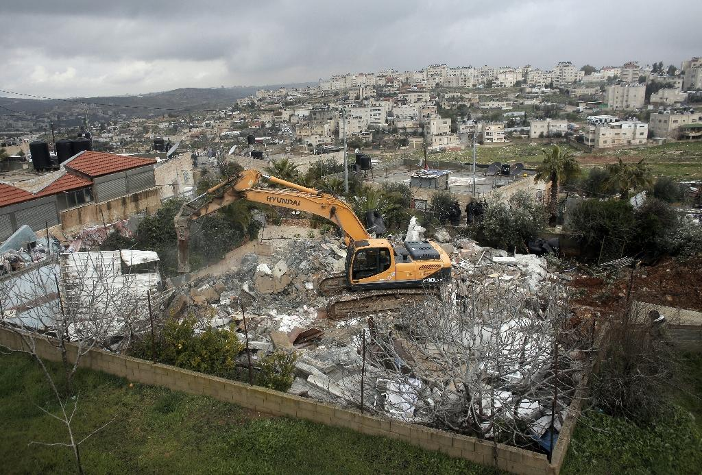 Israeli authorities use heavy machinery to demolish a house belonging to a Palestinian family in the Arab east Jerusalem neighbourhood of Shuafat on January 27, 2016