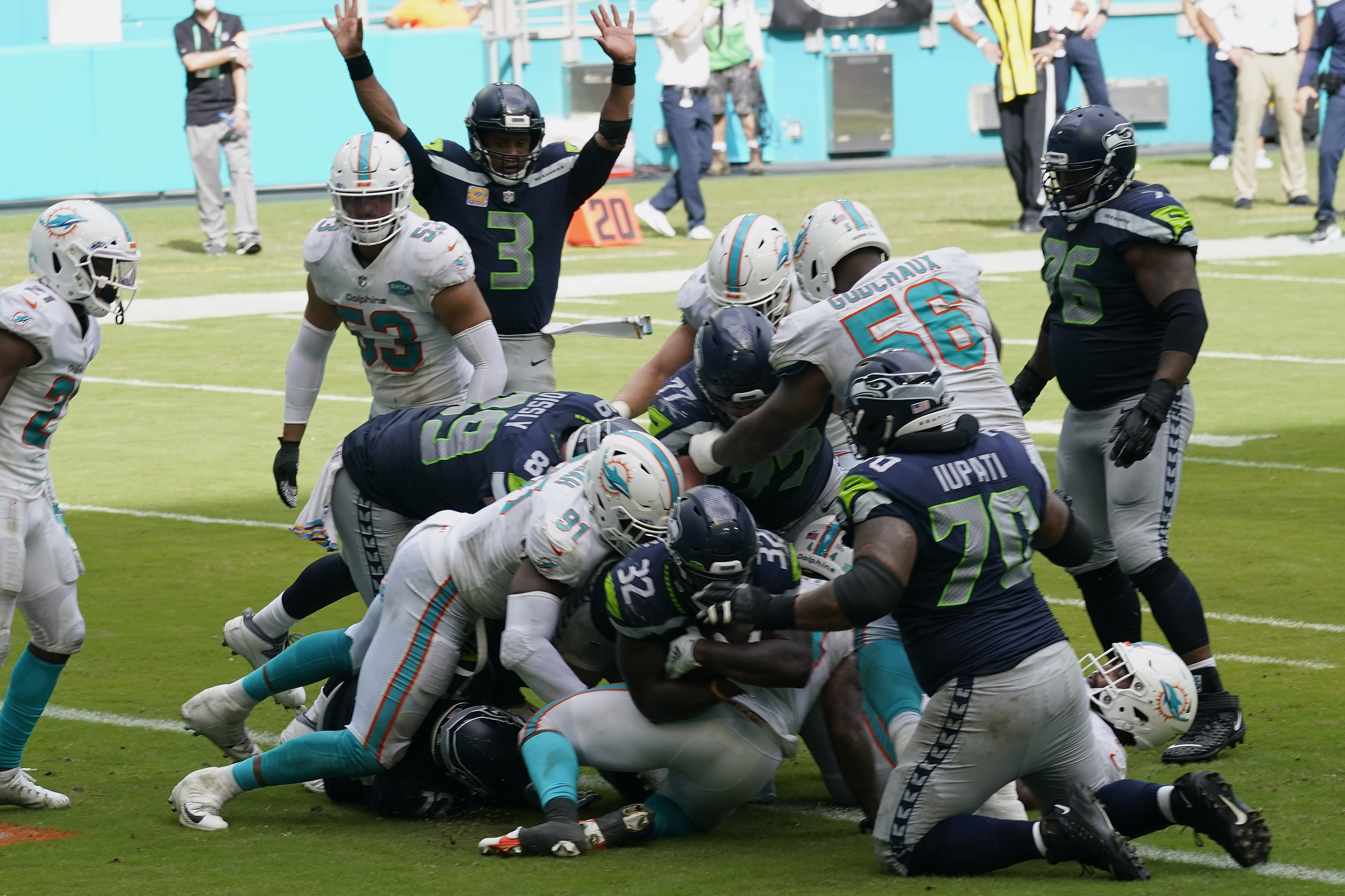 Seattle Seahawks running back Chris Carson (32) scores a touchdown during the second half of an NFL football game against the Miami Dolphins, Sunday, Oct. 4, 2020, in Miami Gardens, Fla. The Seahawks defeated the Dolphins 31-23.(AP Photo/Lynne Sladky)