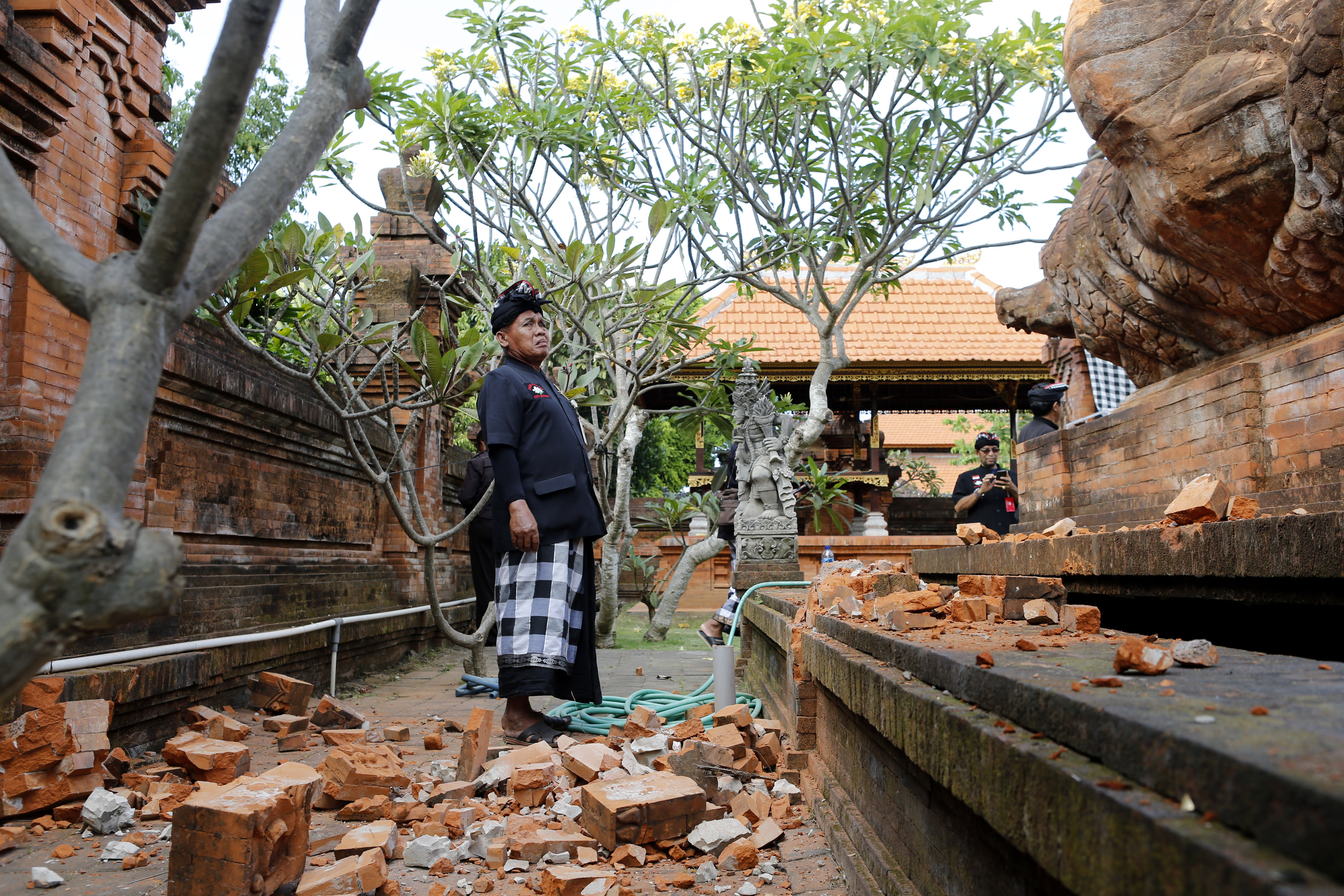 Balinese man stands near a damaged temple in Bali, Indonesia Tuesday, July 16, 2019. Indonesian authorities say a subsea earthquake shook Bali, Lombok and East Java on Tuesday, causing damage to homes and temples. (AP Photo/Firdia Lisnawati)