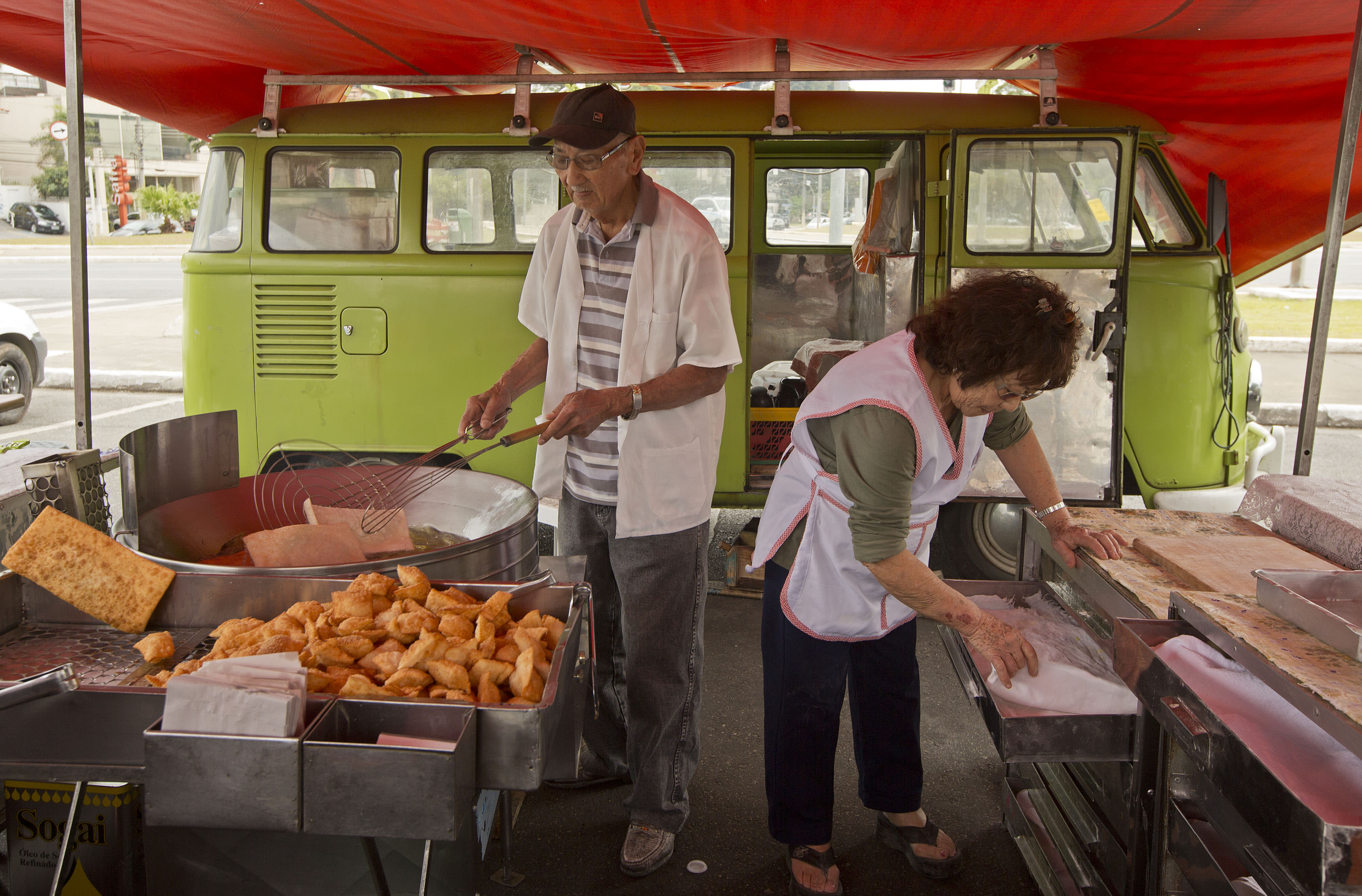 """In this Sept. 3, 2013 photo, Jorge Hanashiro and his wife Ana, prepare deep fried meat and vegetable pastry pies at an open-air market, with their light green 1974 Volkswagon van or Kombi, parked nearby, in Sao Paulo, Brazil. """"There may be safer and more modern cars around, but for me the Kombi is the best vehicle to transport my stall and products to the six open air markets I visit each week,"""" the 77-year-old Hanashiro said. """"It is economical, rugged and easy to repair."""" (AP Photo/Andre Penner)"""