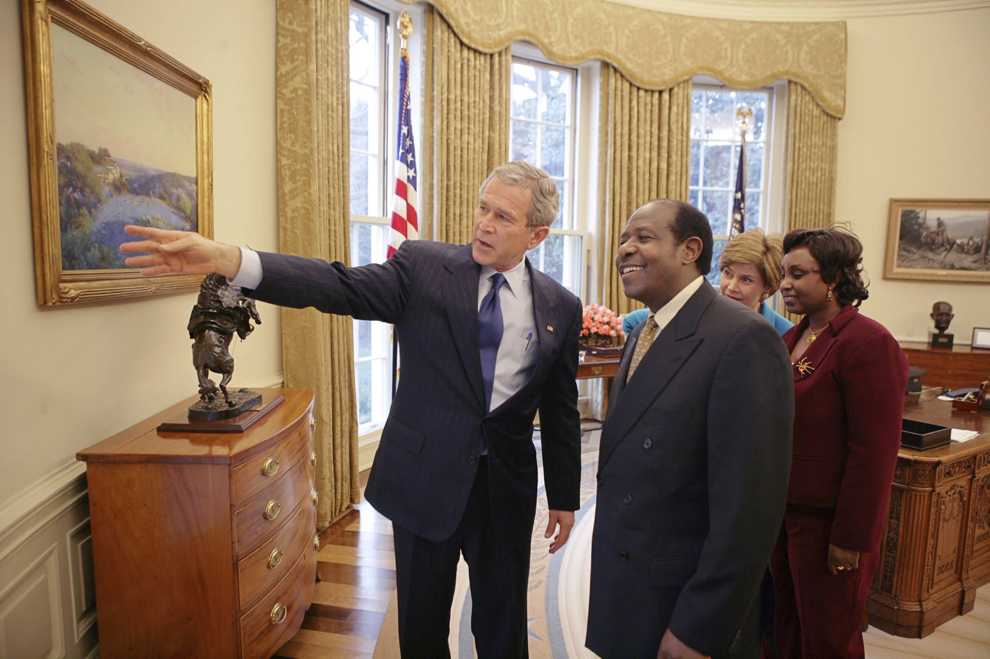 """FILE - In this Thursday, Feb. 17, 2005 file photo provided by the White House, President Bush, left, and first lady Laura Bush, 2nd right, meet with Paul Rusesabagina, center-right, and his wife, Tatiana, right, in the Oval Office. Paul Rusesabagina, who was portrayed in the film """"Hotel Rwanda"""" as a hero who saved the lives of more than 1,200 people from the country's 1994 genocide, and is a well-known critic of President Paul Kagame, has been arrested by the Rwandan government on terror charges, police announced on Monday, Aug. 31, 2020.(Eric Draper/The White House via AP )"""