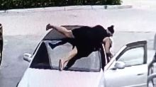CCTV footage shows woman dive on top of car after having bag stolen