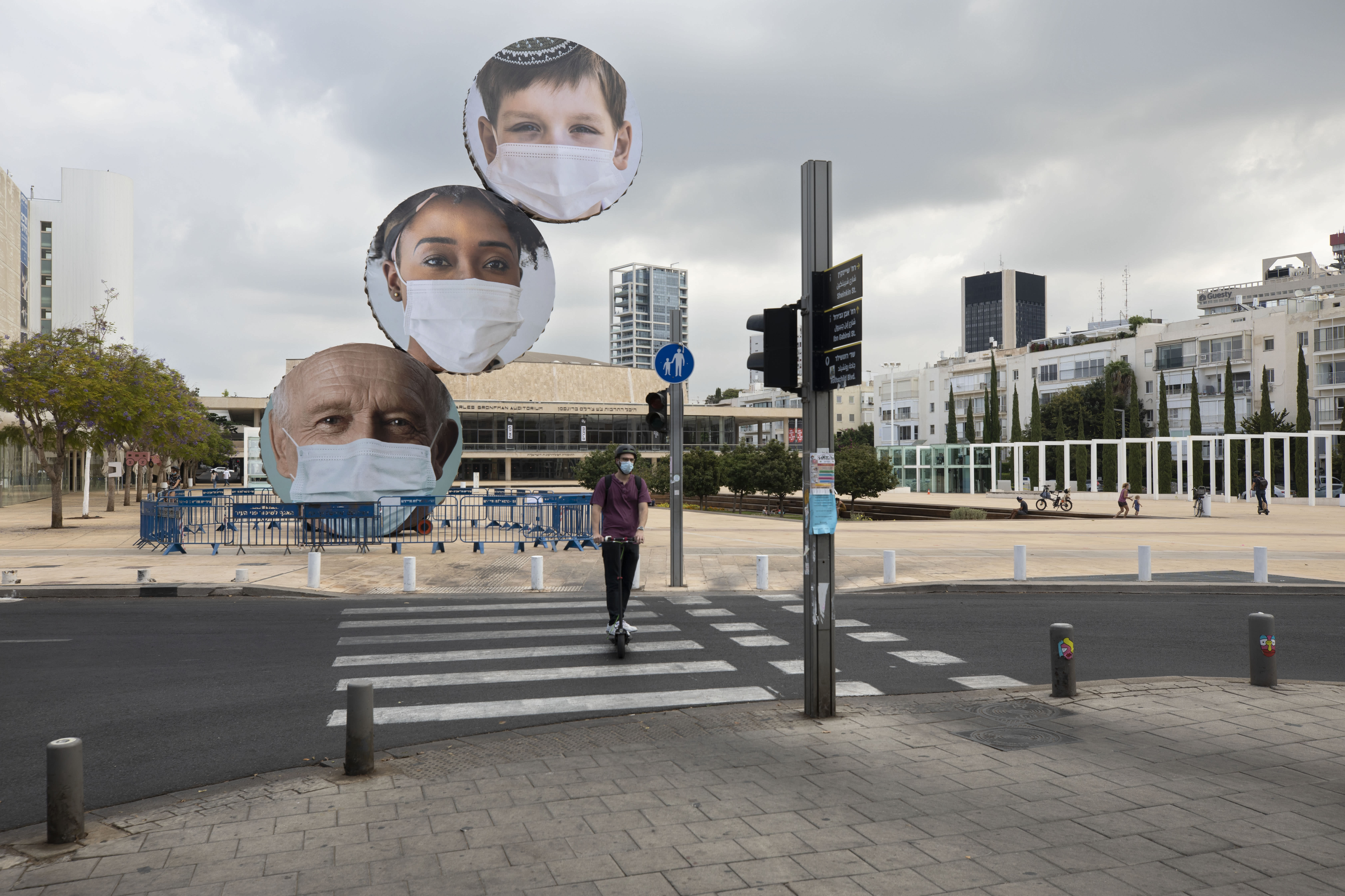 An Israeli woman rides past banners encouraging people to wear face masks in Tel Aviv, Israel, Thursday, Sept. 24, 2020. Israeli Prime Minister Benjamin Netanyahu on Wednesday announced plans for a strict, two-week nationwide lockdown in a bid to slow a raging coronavirus outbreak. (AP Photo/Sebastian Scheiner)