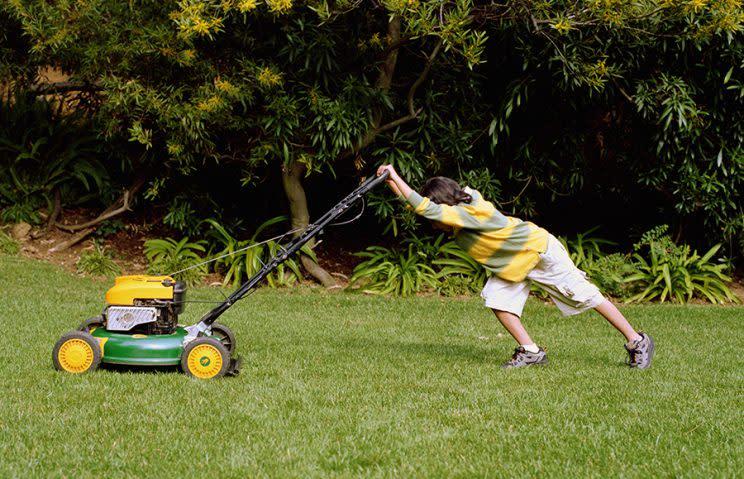 Boy (8-10) mowing lawn
