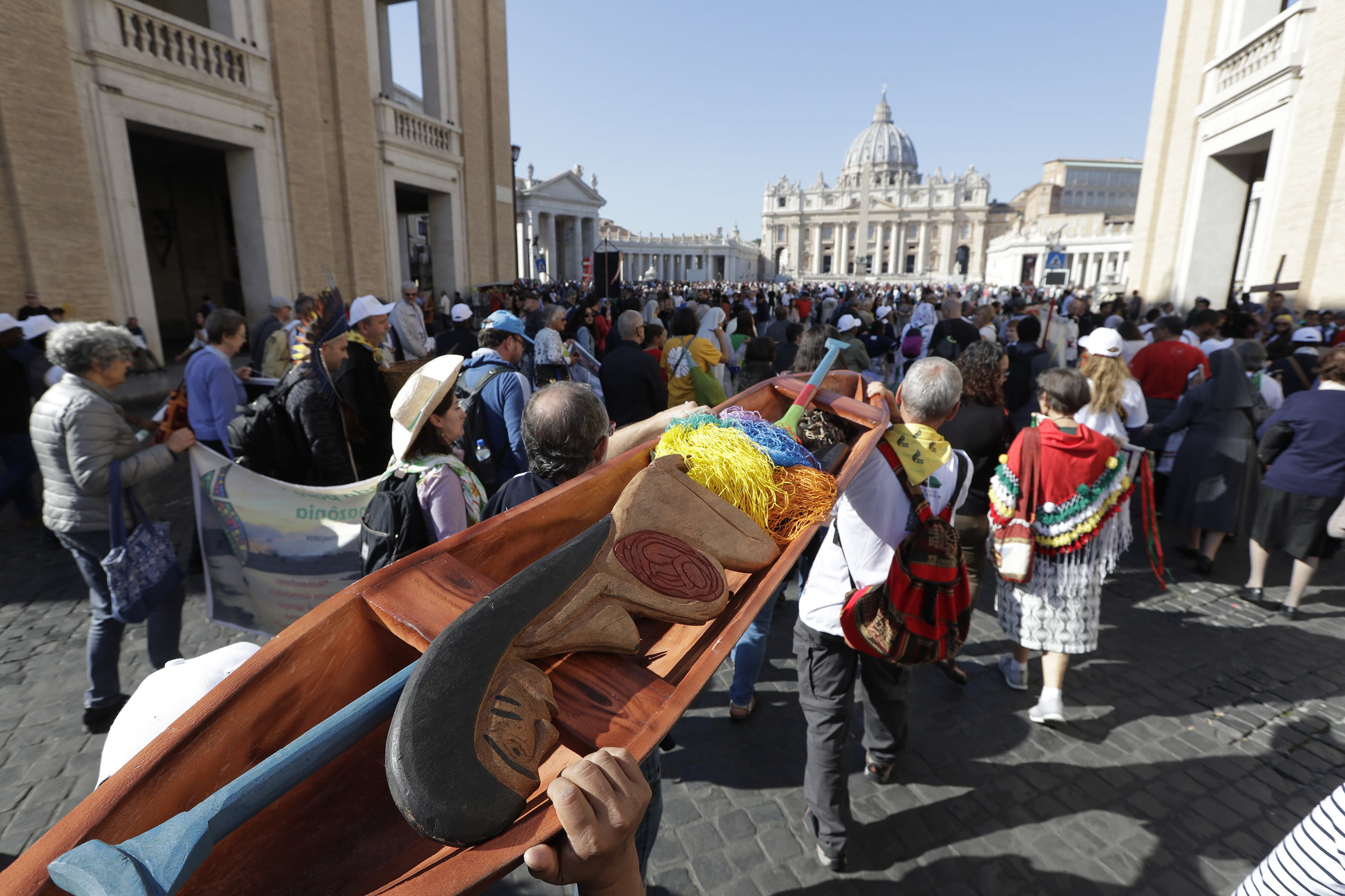 In this photo taken on Saturday, Oct. 19, 2019, members of Amazon indigenous populations walk during a Via Crucis (Way of the Cross) procession from St. Angelo Castle to the Vatican. In foreground is a wooden statue portraying a naked pregnant woman. Pope Francis' meeting on the Amazon is wrapping up after three weeks of debate over married priests, the environment _ and the destruction of indigenous statues that underscored the willingness of conservatives to violently vent their opposition to the pope. (AP Photo/Andrew Medichini)