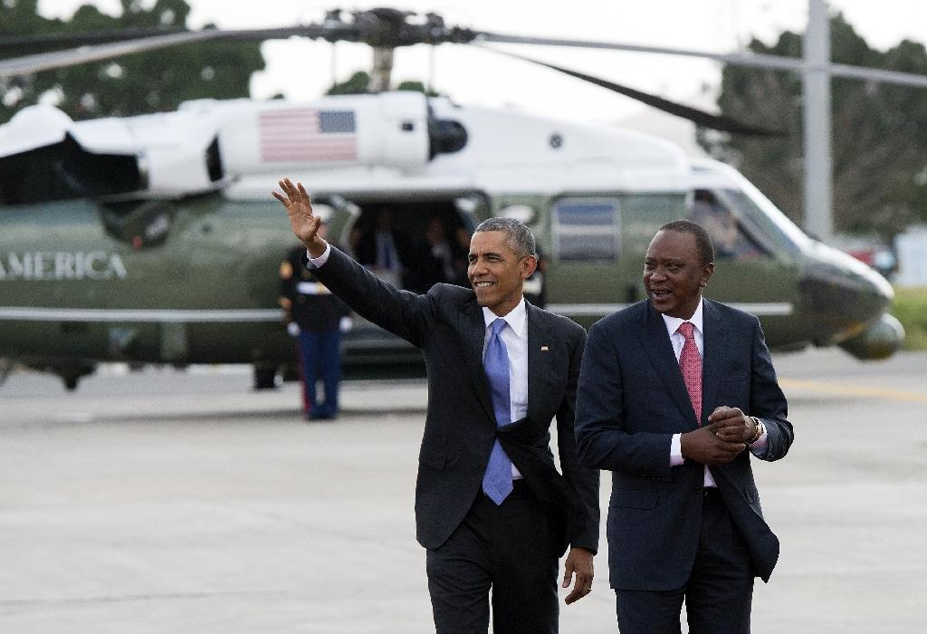 US President Barack Obama waves alongside his Kenyan counterpart Uhuru Kenyatta (R) before boarding Air Force One prior to his departure on July 26, 2015 (AFP Photo/Saul Loeb)
