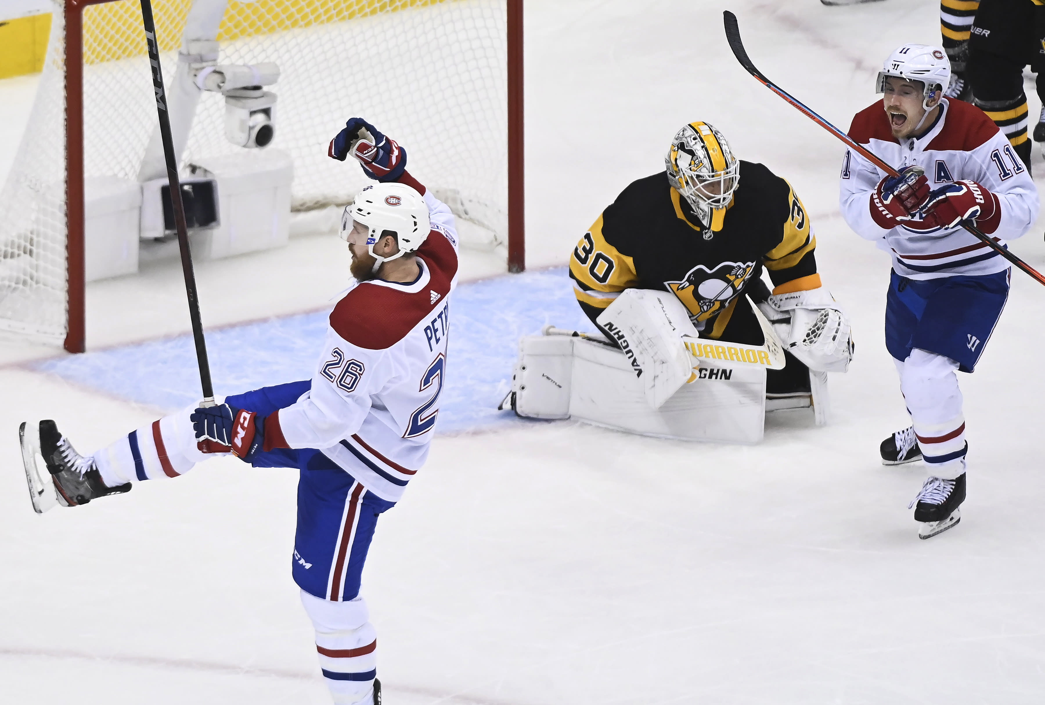 Montreal Canadiens defenseman Jeff Petry (26) celebrates along with right wing Brendan Gallagher (11) after scoring against Pittsburgh Penguins goaltender Matt Murray (30) during overtime in an NHL hockey playoff game in Toronto, Saturday, Aug. 1, 2020. (Nathan Denette/The Canadian Press via AP